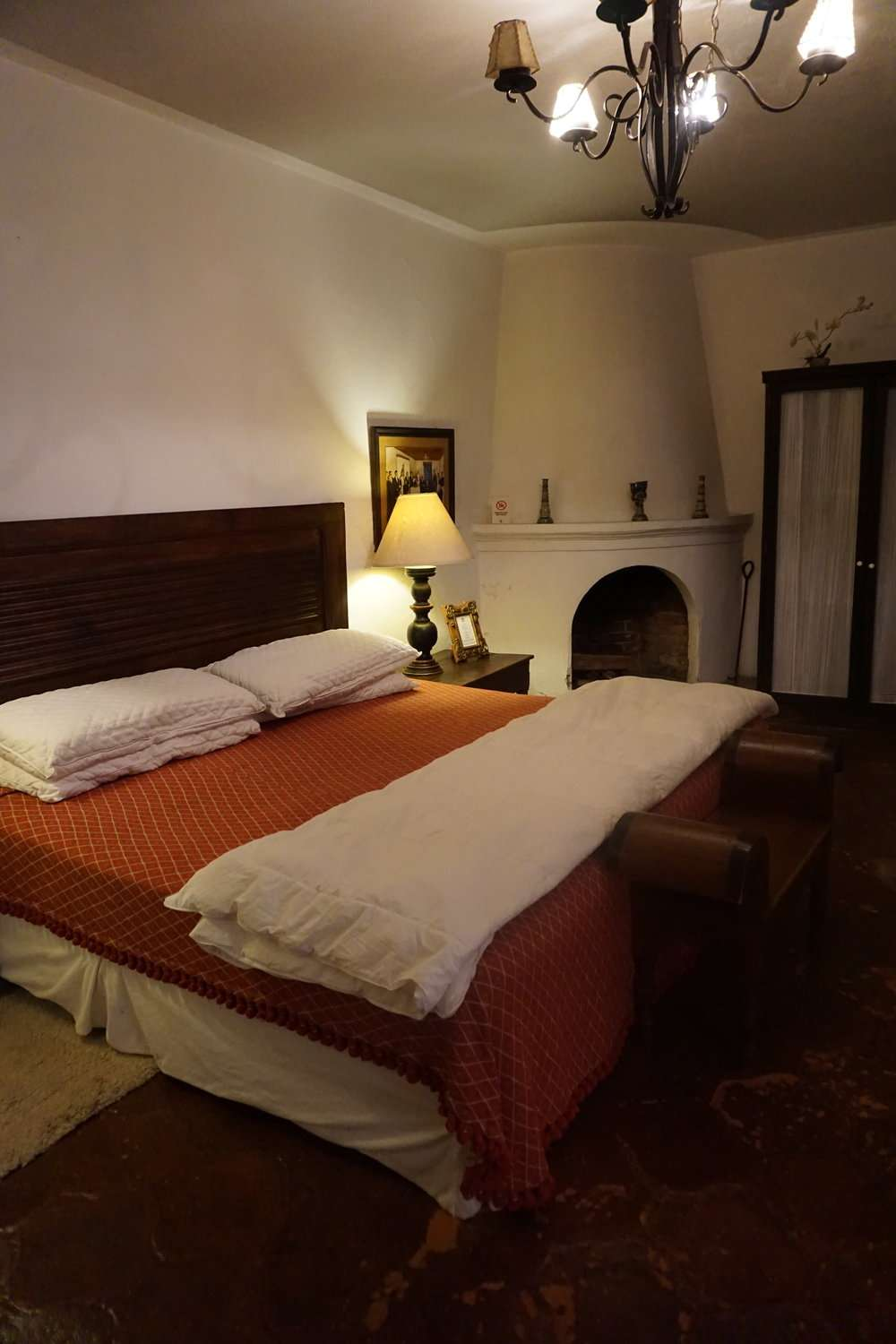 large bed with terracotta coloured bedding at Casa Capuchinas in Antigua