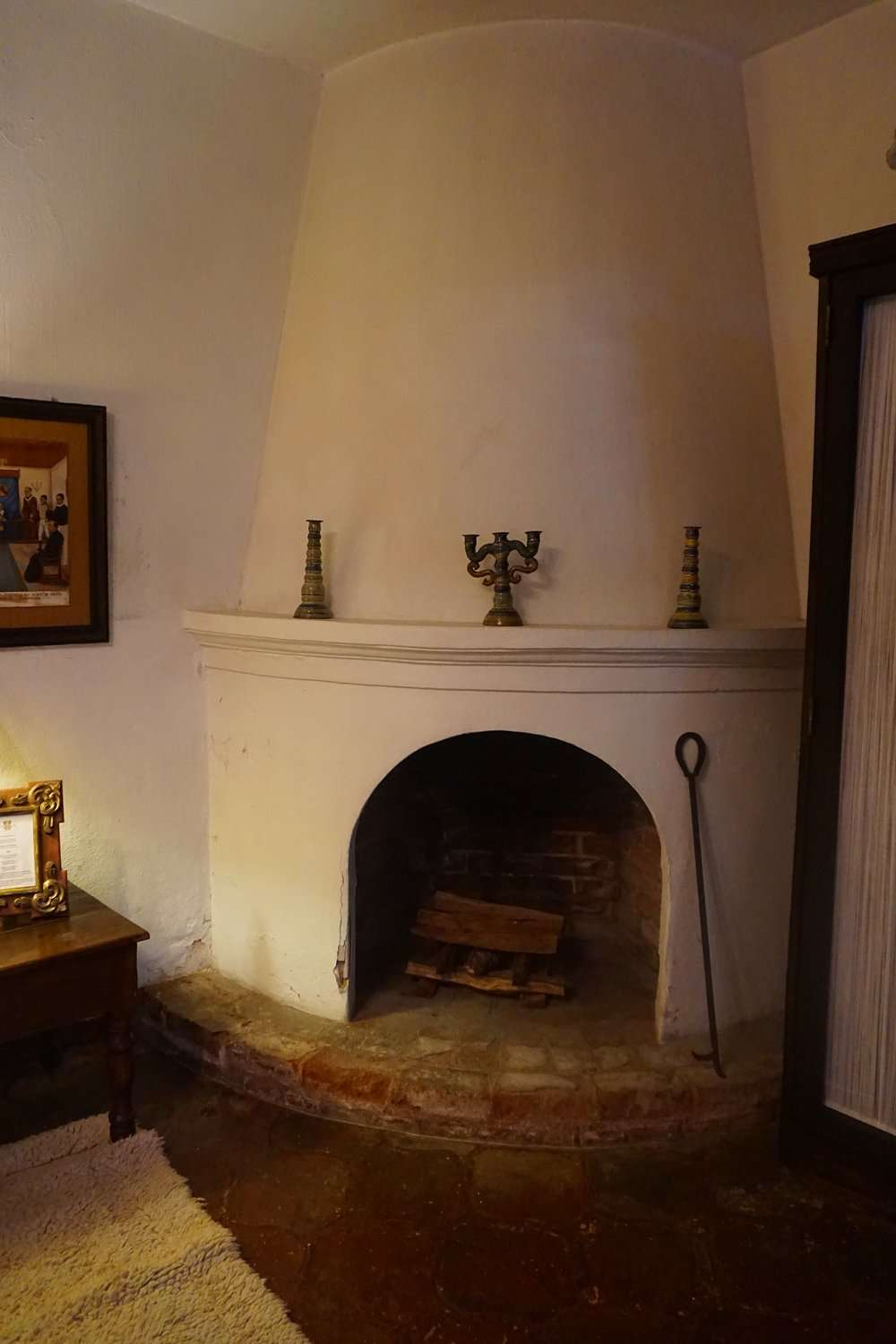 large corner fireplace, painted white, in a bedroom at Casa Capuchinas