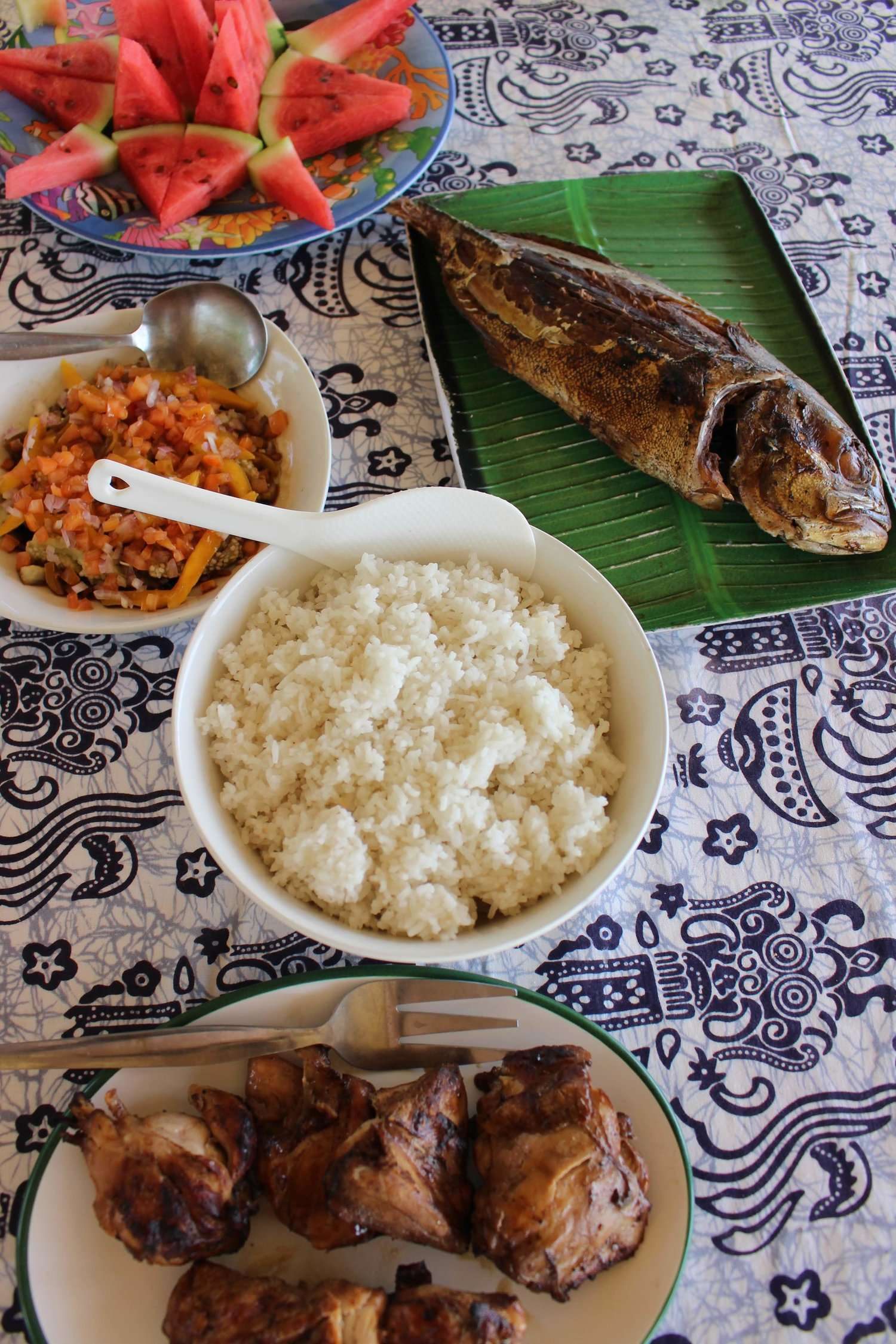 a spread of fresh cooked fish, rice and watermelon - lunch during an island hopping tour in Coron with Casa Fidelis