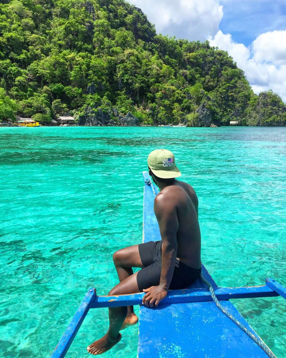 man sits on the front of a blue wooden boat, with bright turquoise water in Coron