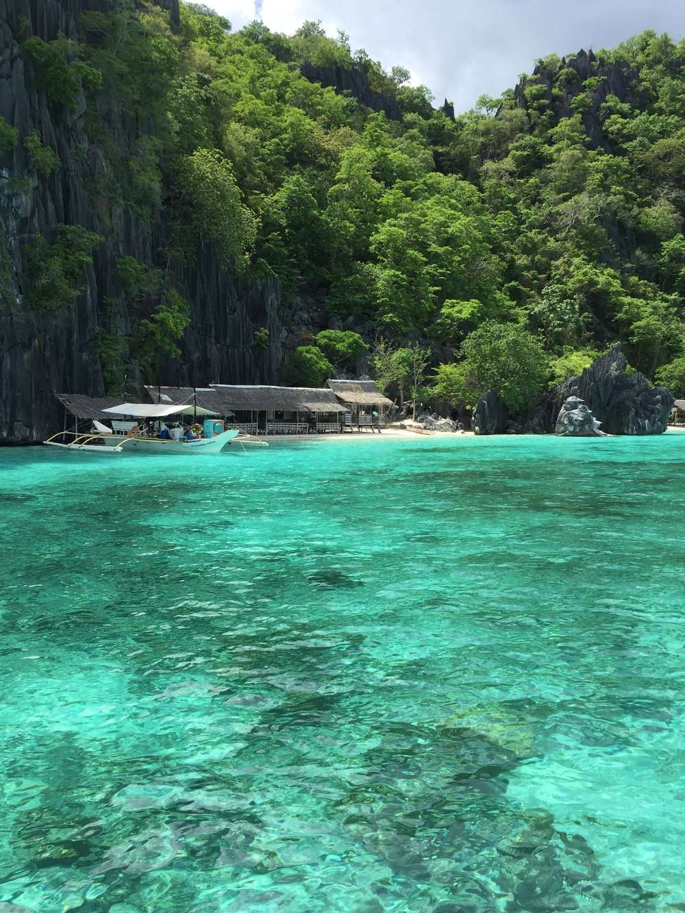 tropical island with wooden beach huts in Coron, Philippines