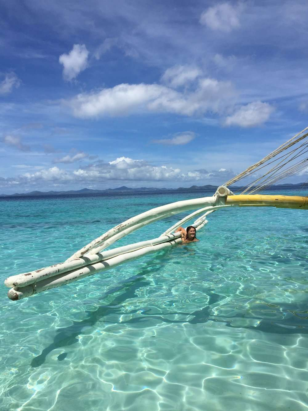 Blue sky and turquoise water with a wooden boat. A lady holds onto the boat from in the water