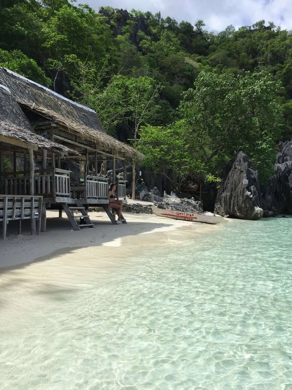 beautiful beach with blue water. A lady in a bikini sits at the edge of a wooden beach hut, during a tour with Casa Fidelis in Coron