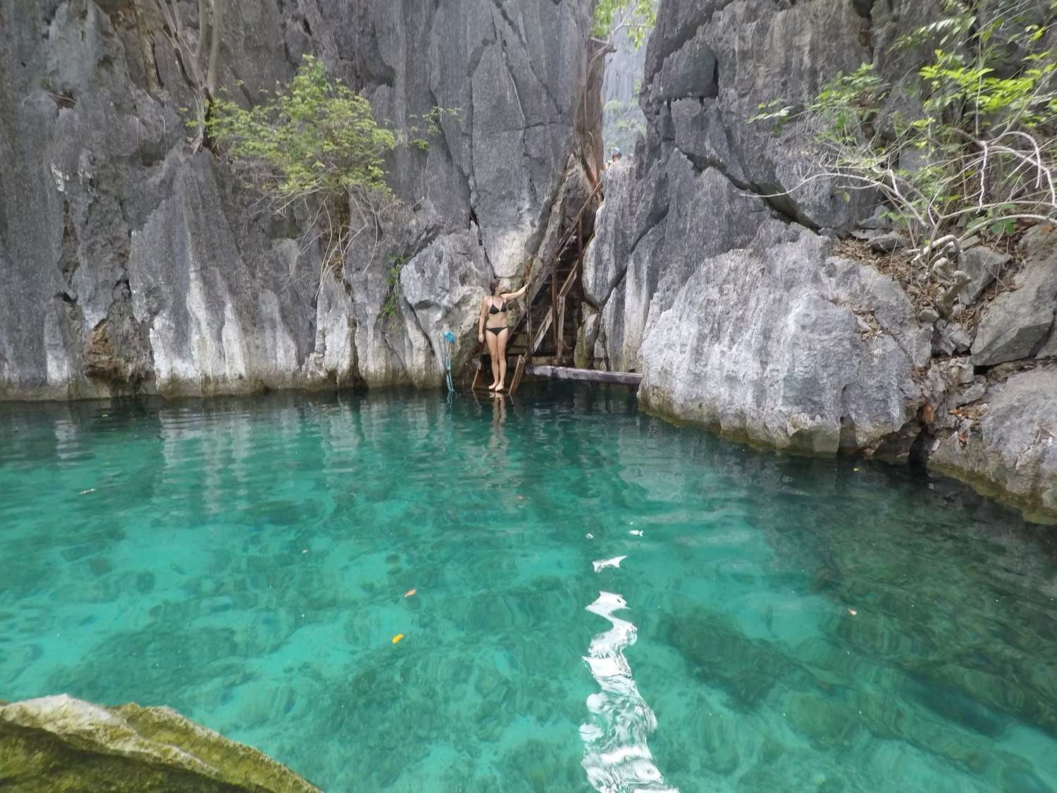 lady stands on a step between the Twin Lagoons in Coron