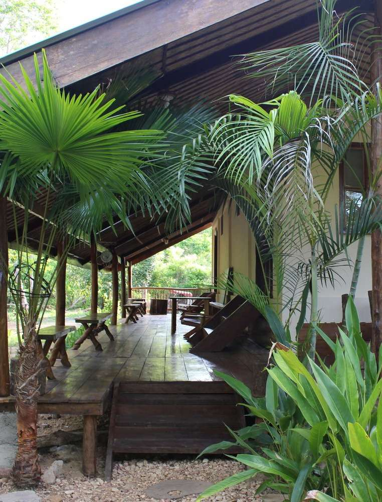 rainforest lodge at Casa Fidelis, a wooden lodge with large veranda, surrounded by lush greenery