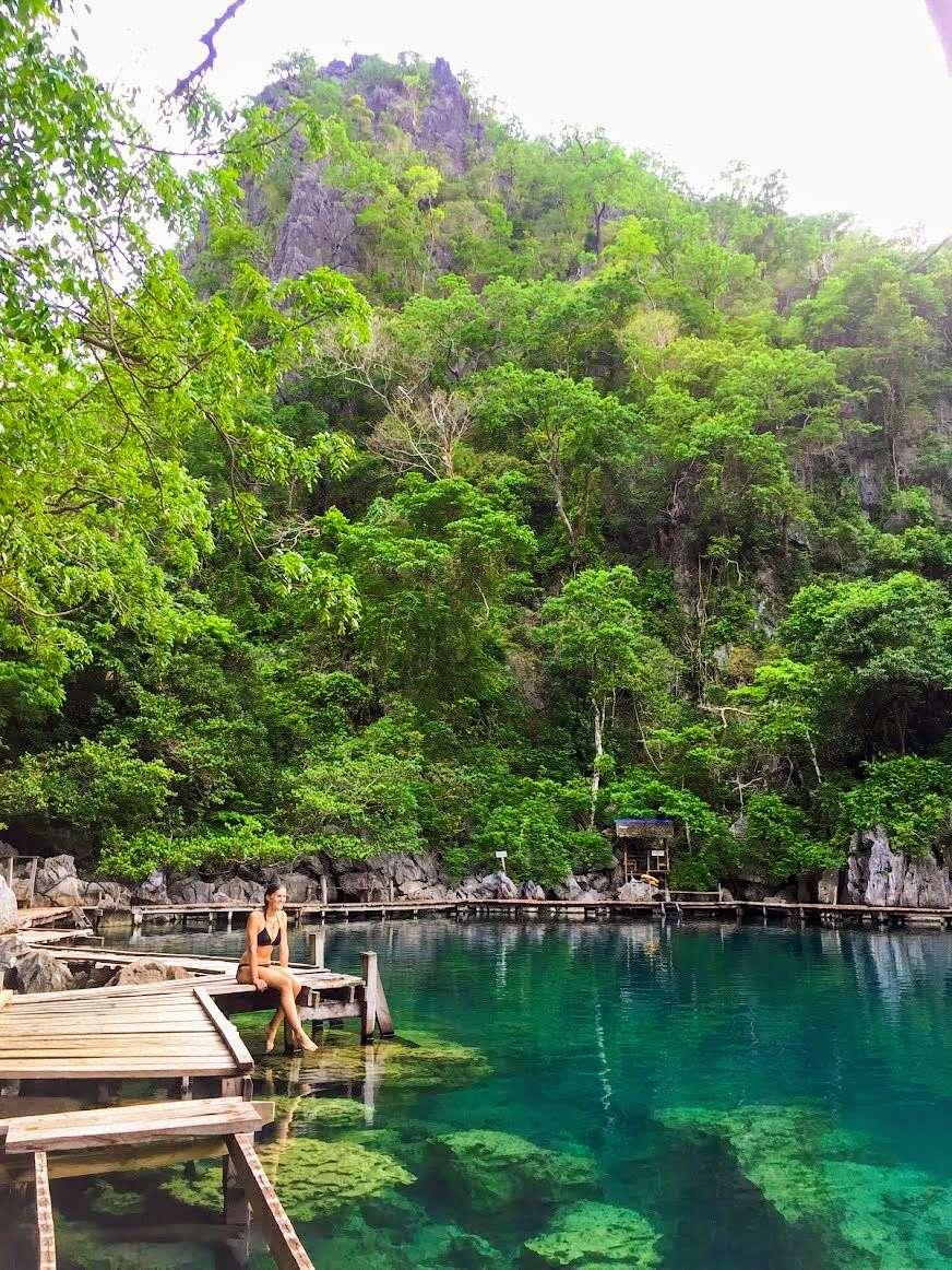 lady wearing a bikini sits on the edge of a wooden walkway along a blue lagoon, Kayangan Lake in Coron, Philippines