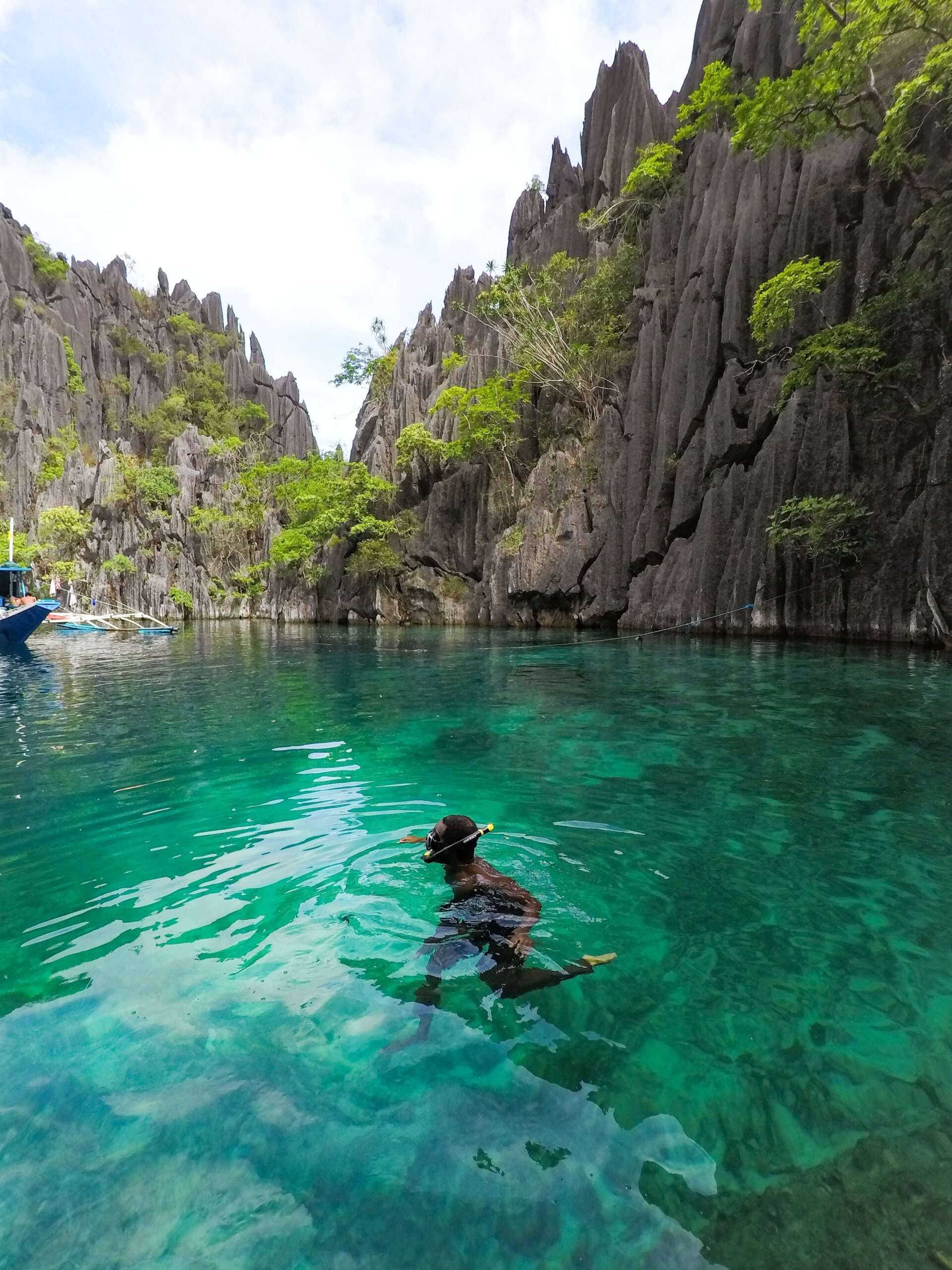 a man treads water in turquoise water surrounded by karst rocks, island hopping in coron