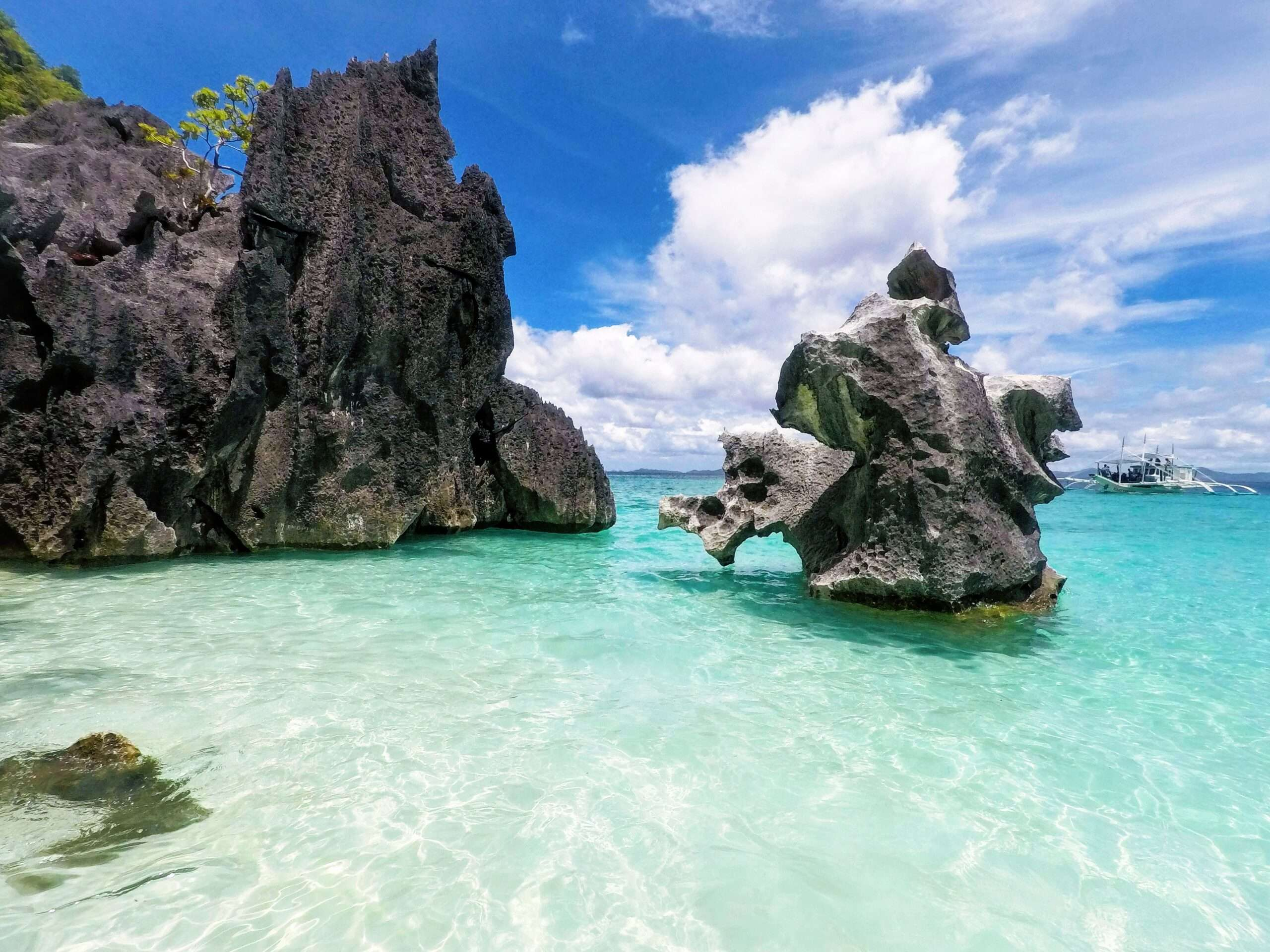 bright blue sky and clear turquoise water with 2 big rock formations in Coron, Philippines