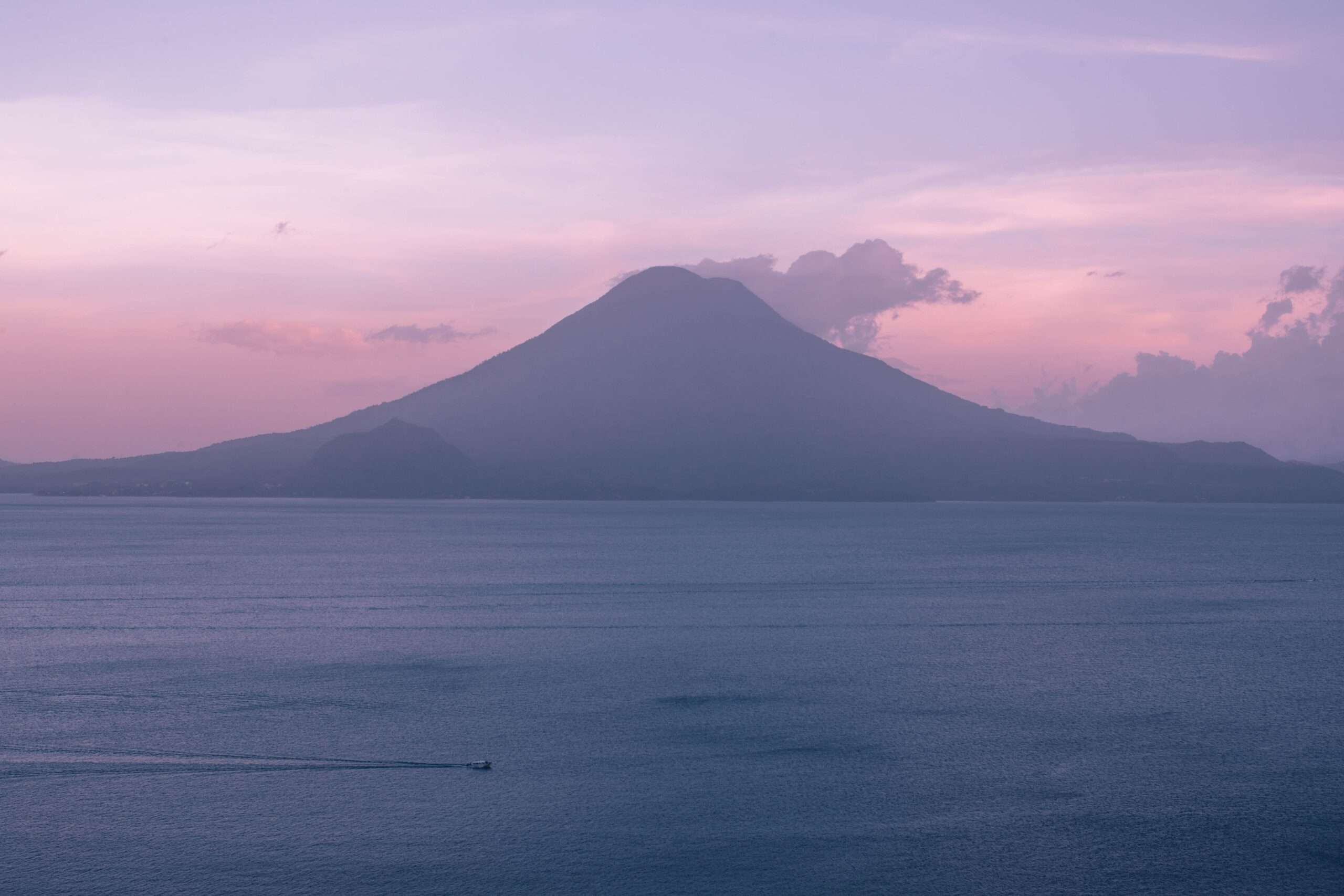 pink and purple sky behind a volcano at the edge of Lake Atitlan