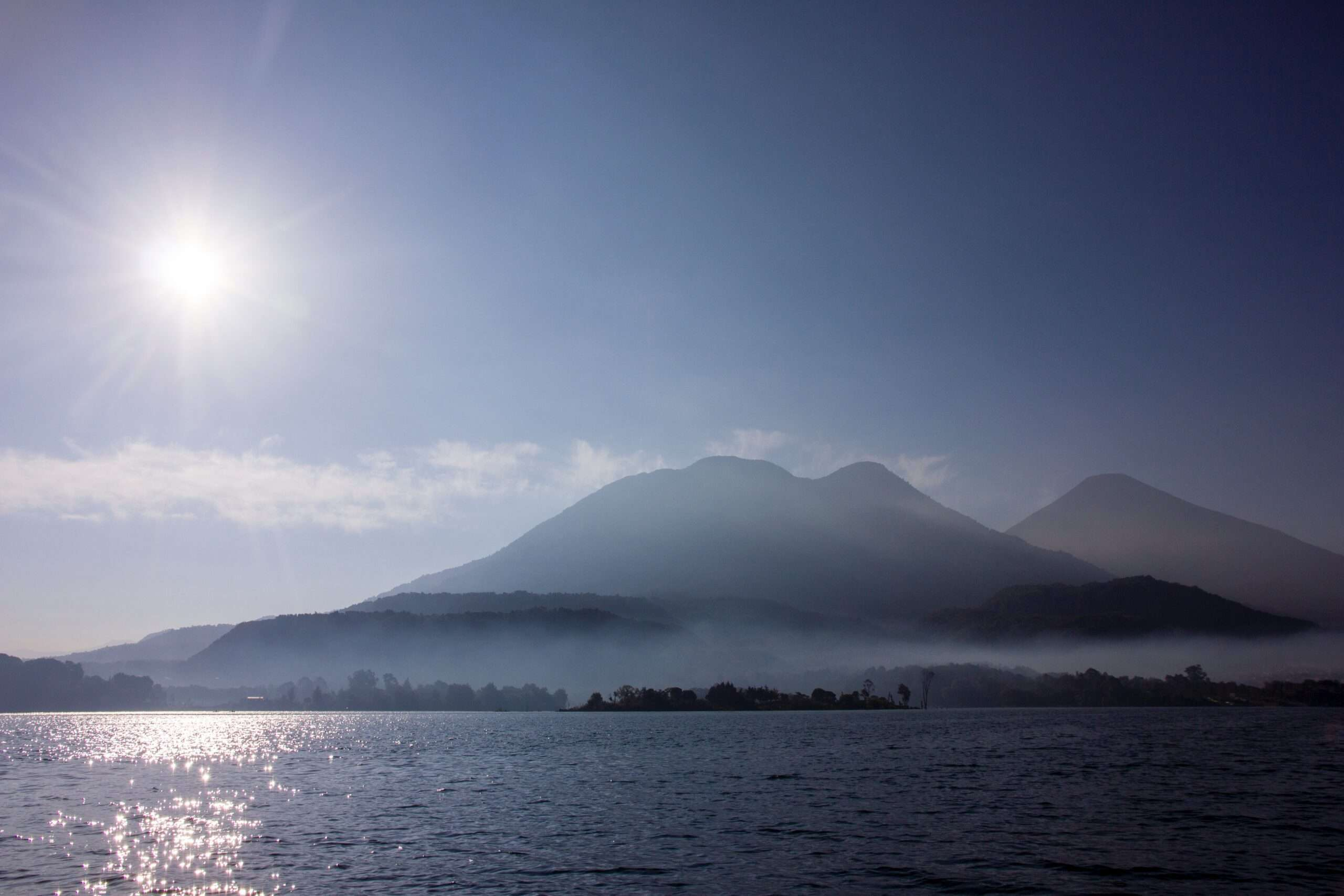 sun high in the sky over the volcano and water at Lake Atitlan