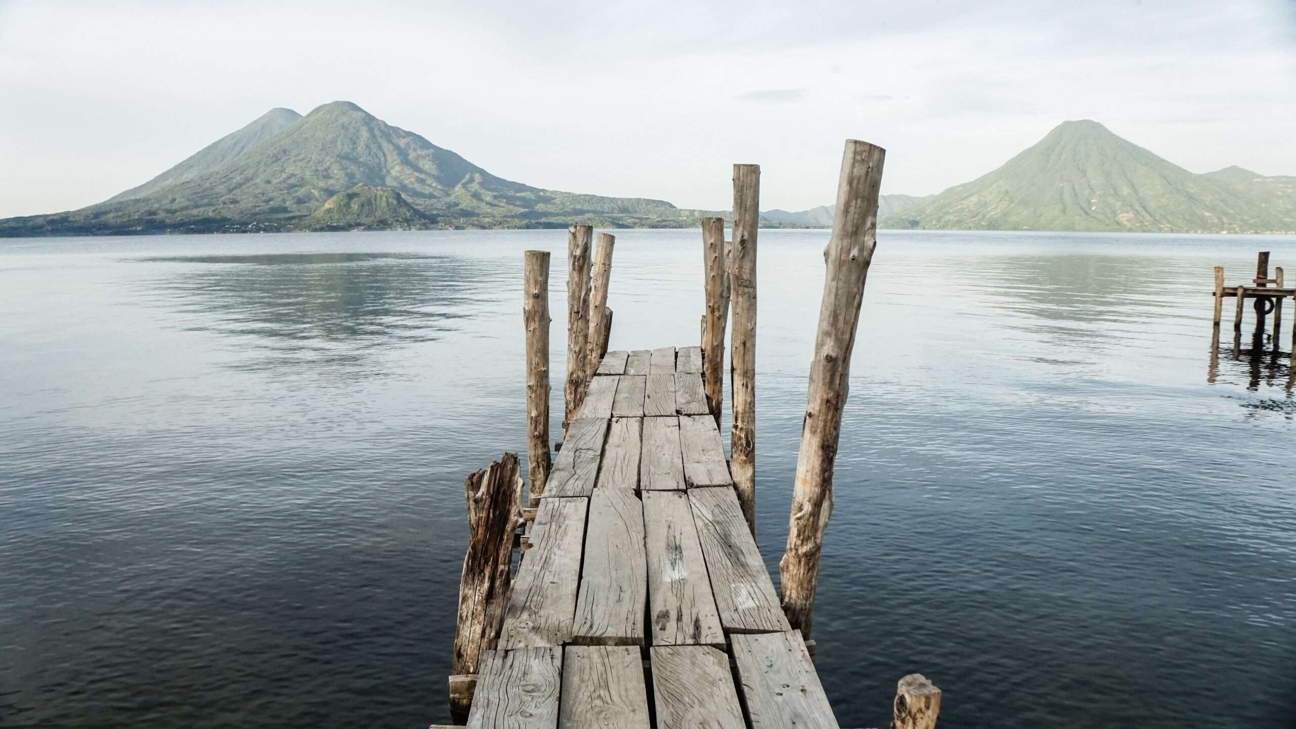 a rickety wooden dock reaches out over the water in Lake Atitlan Guatemala