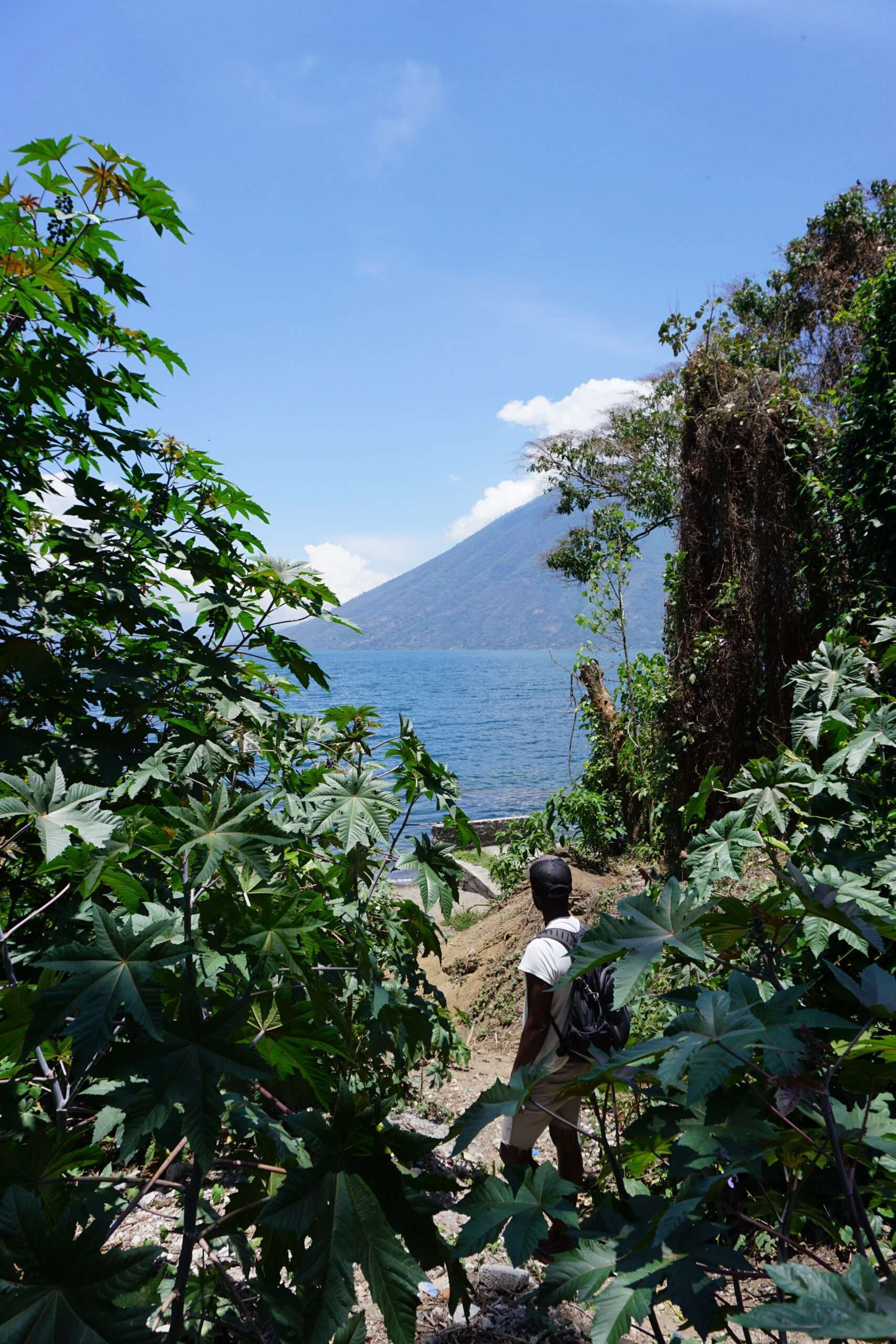 man with a backpack amongst the trees, looking out to the water and volcano at Lake Atitlan