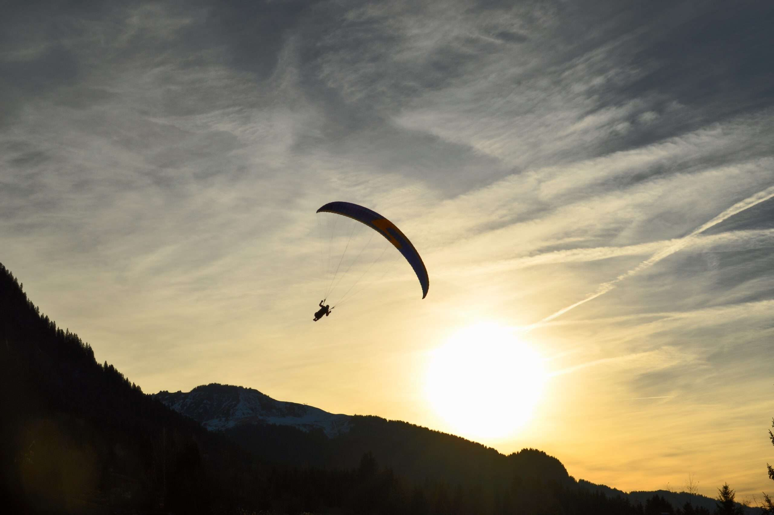 paraglider over the hills at sunset, one of the best things to do in Lake Atitlan