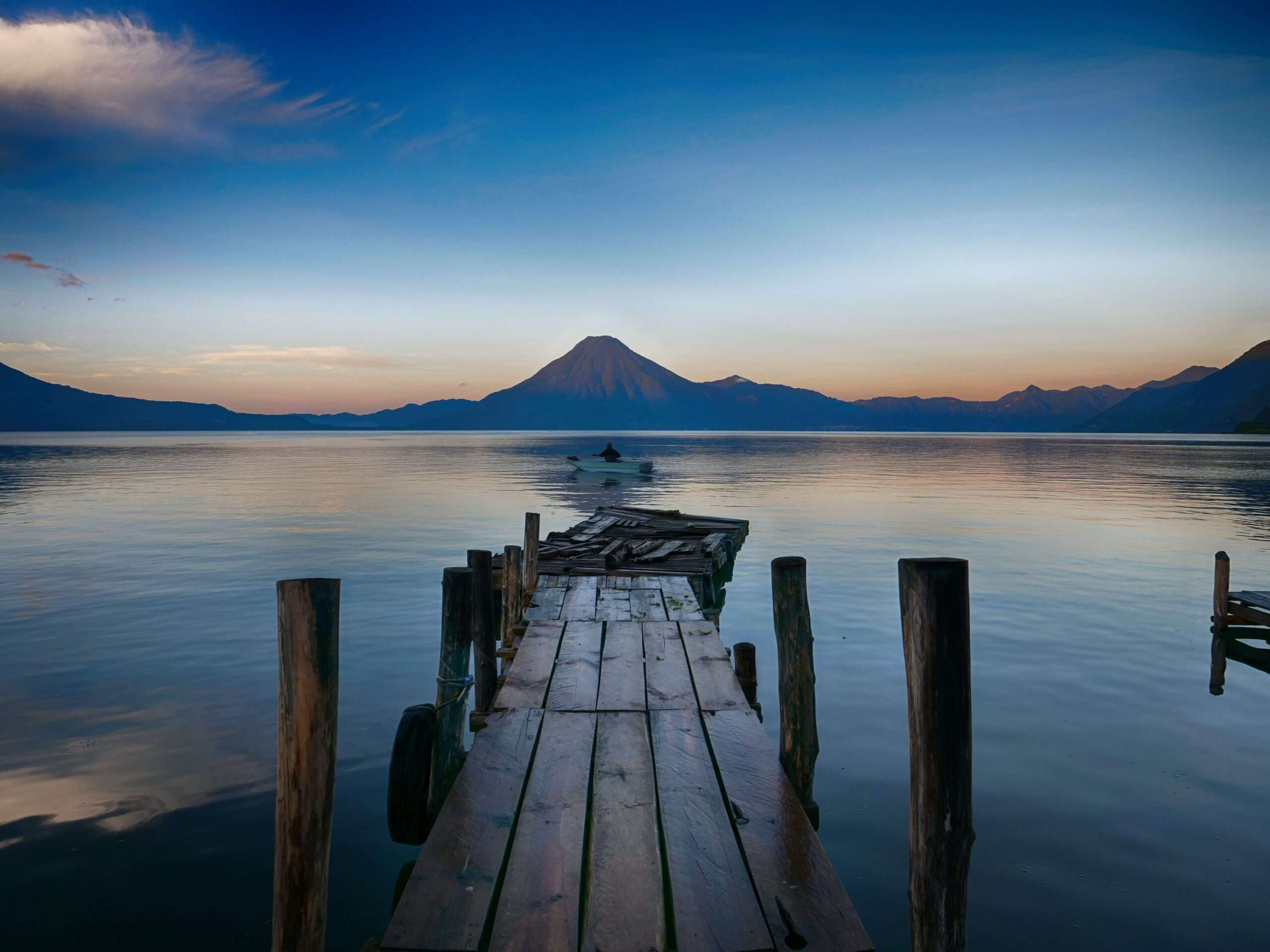 wooden dock over the water, as the sun rises behind a volcano and over Lake Atitlan
