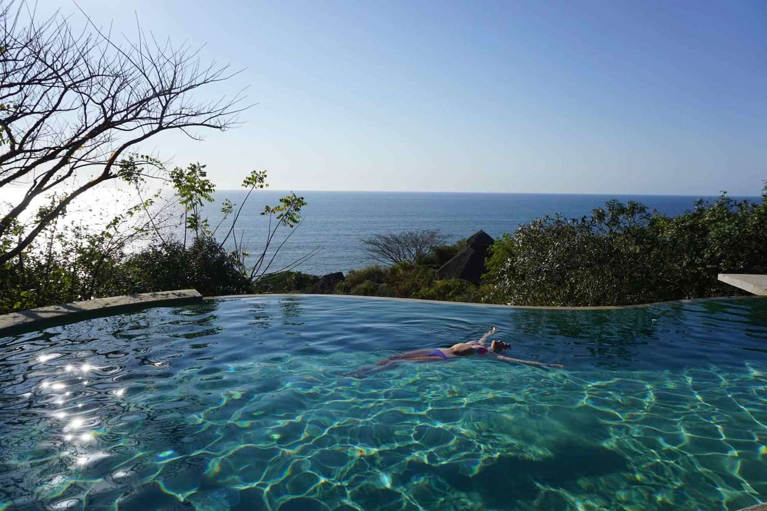 Woman floats in the infinity pool at Haramara Retreat