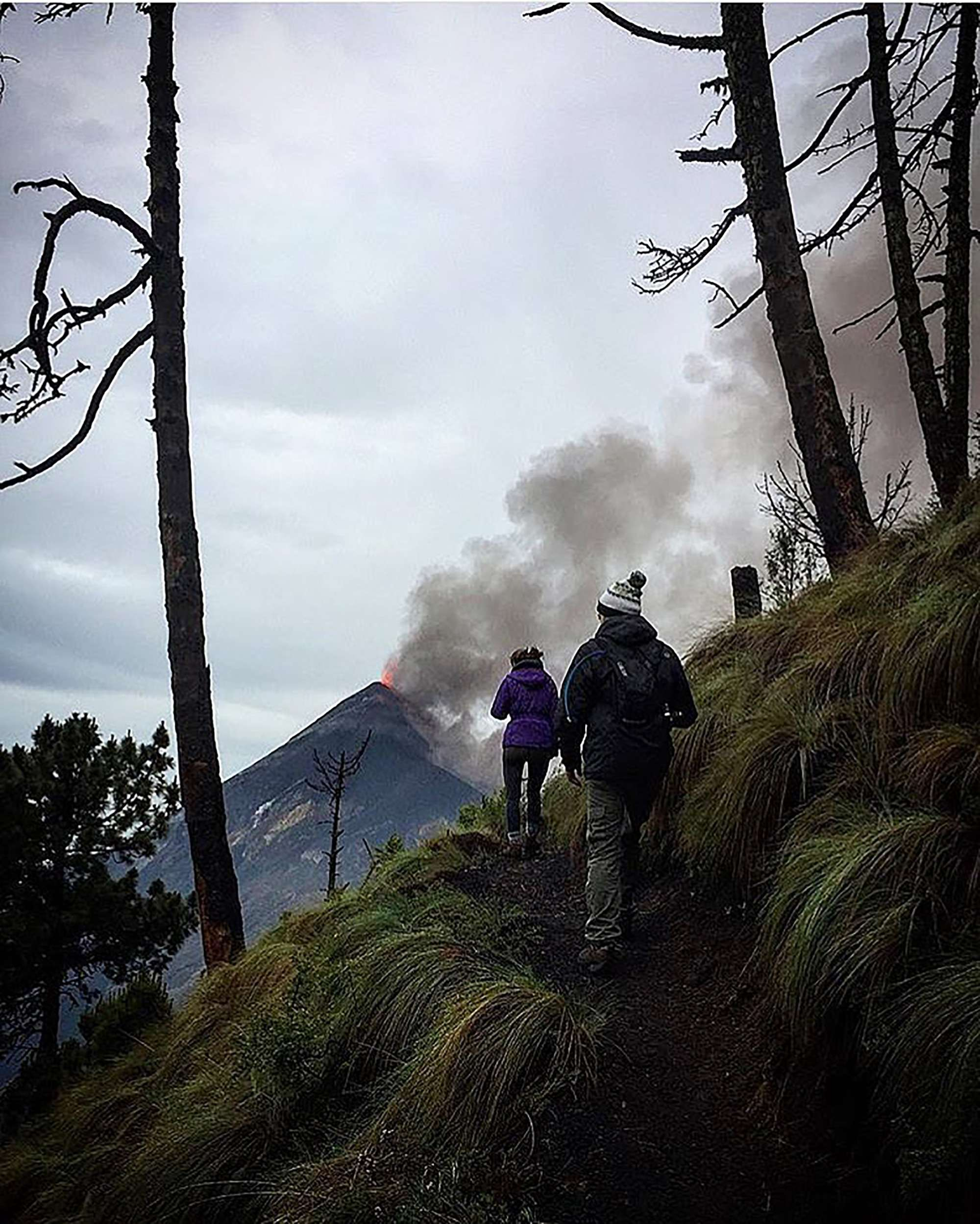 Two hikers on the trail up Acatenango volcano with an erupting Fuego volcano in the distance