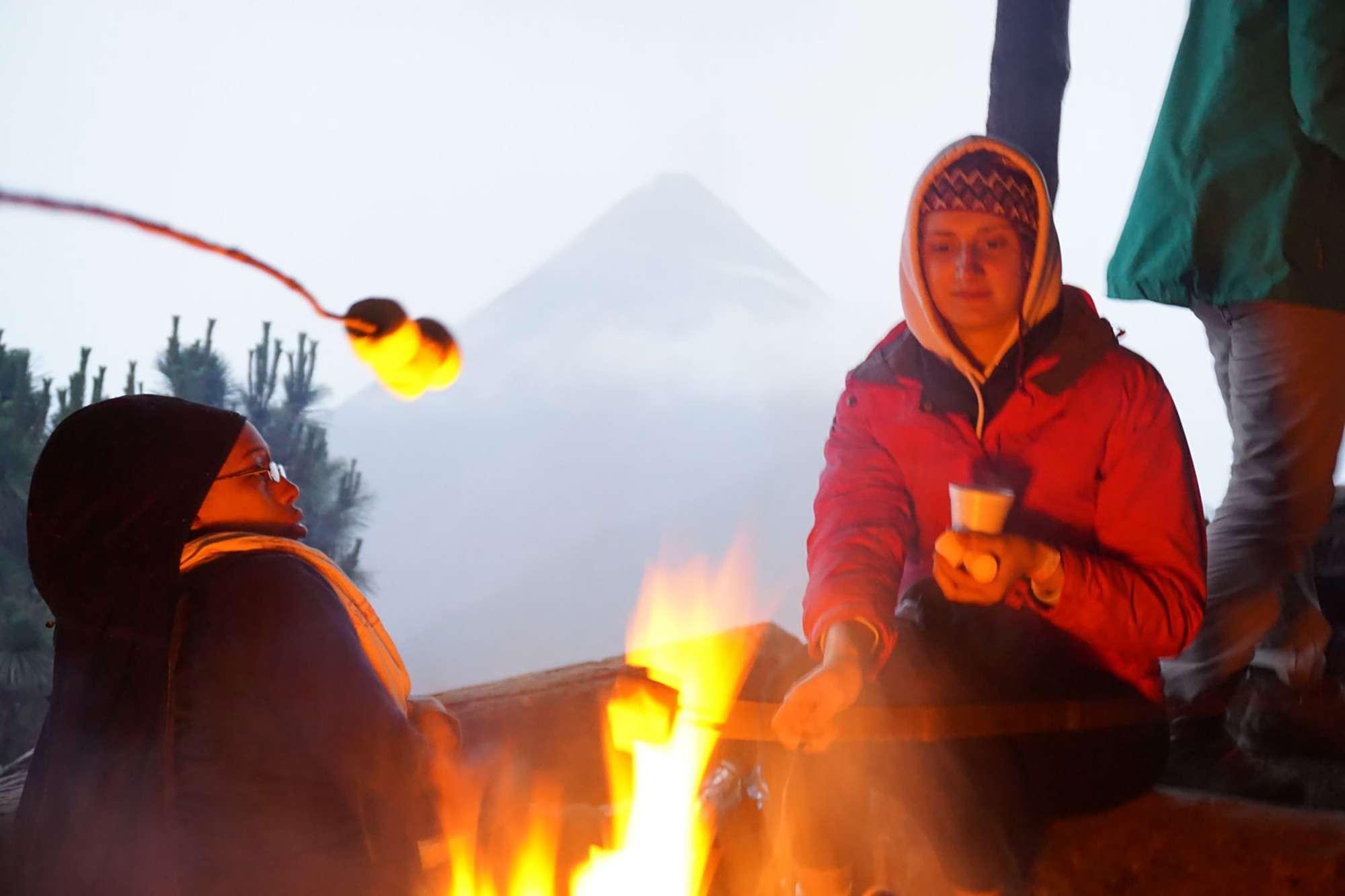 Woman roasts marshmallows at base camp during the hike up Acatenango Volcano
