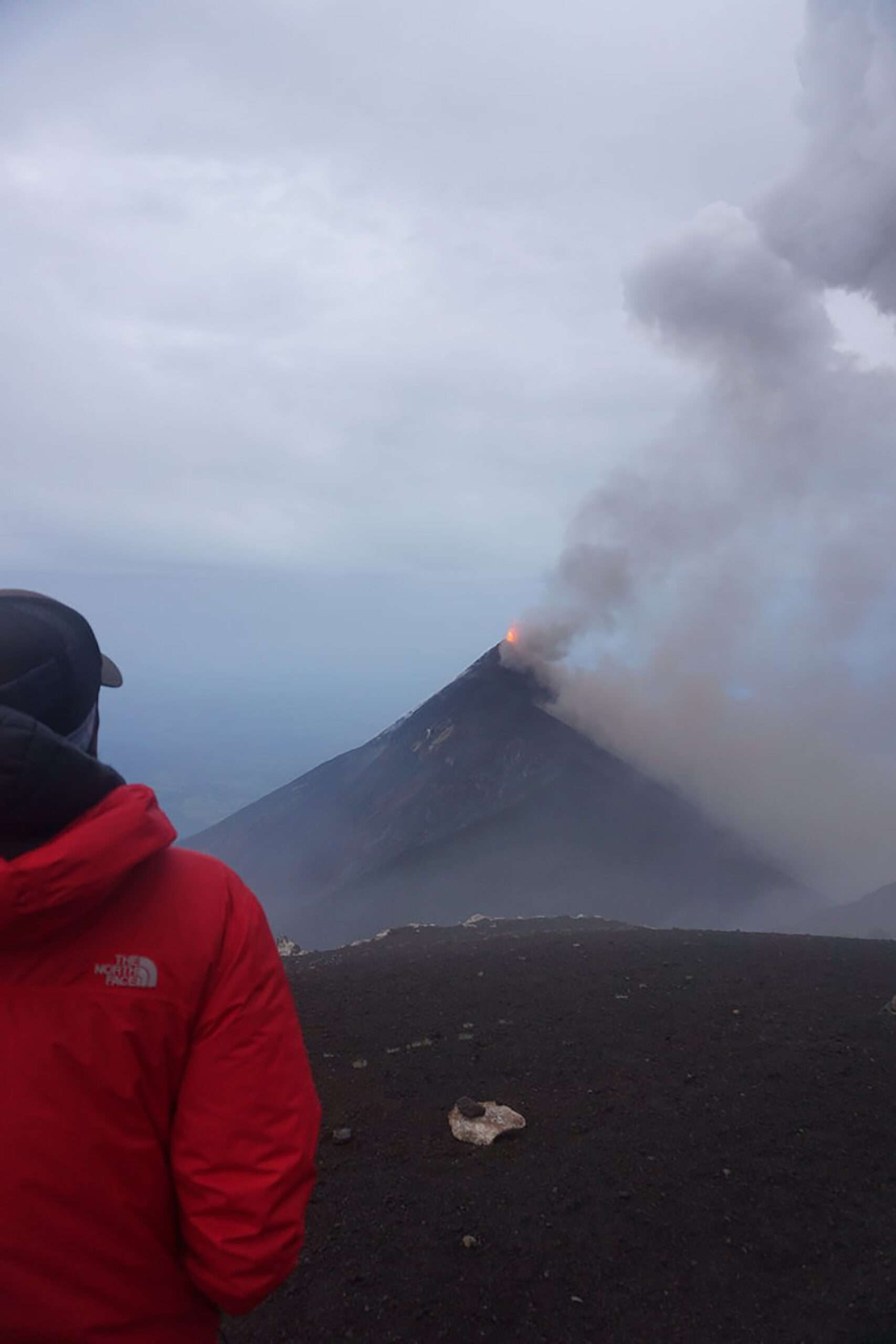 A hiker watches eruption of Fuego Volcano in the distance
