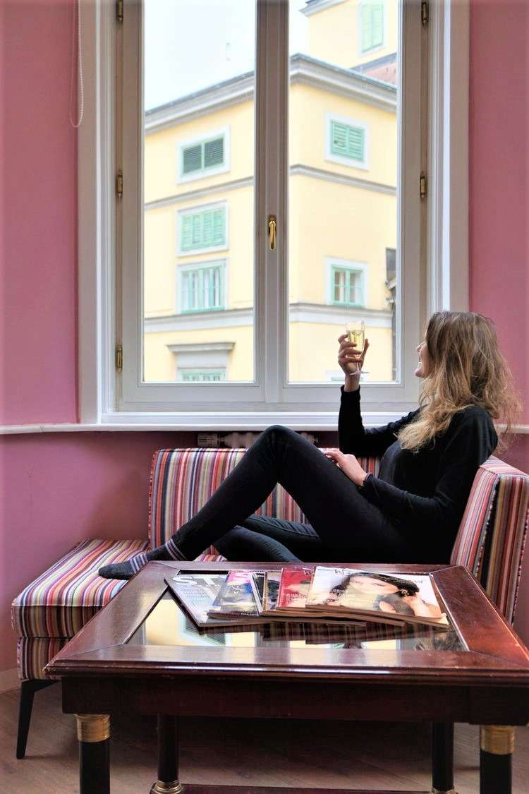 Woman sits in Bedroom window seat at Hotel Beethoven Vienna, Austria