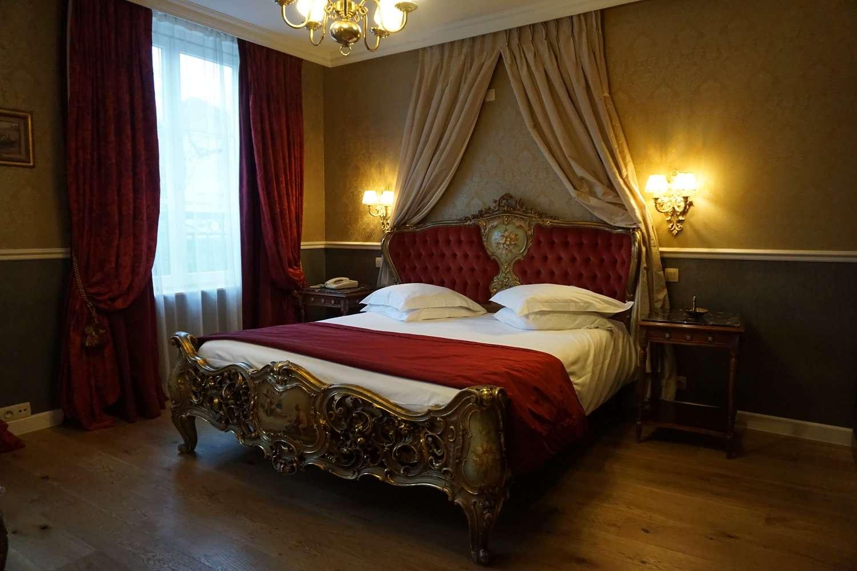 Grand bed in guestroom at Hotel Die Swaene in Bruges