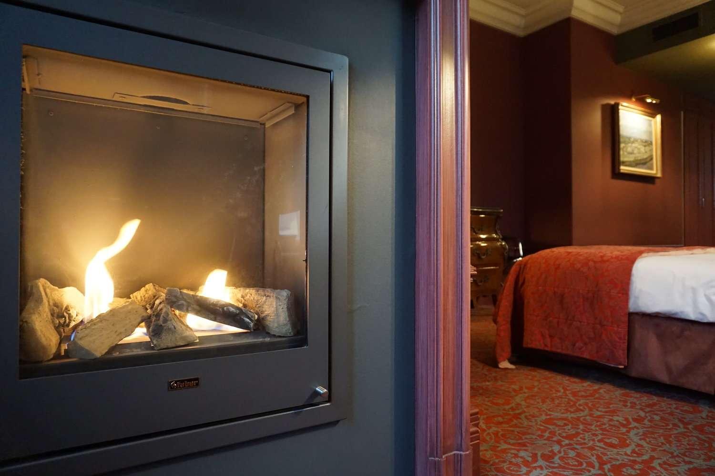 Lit fireplace flickers in guest room at Hotel Die Swaene in Bruges