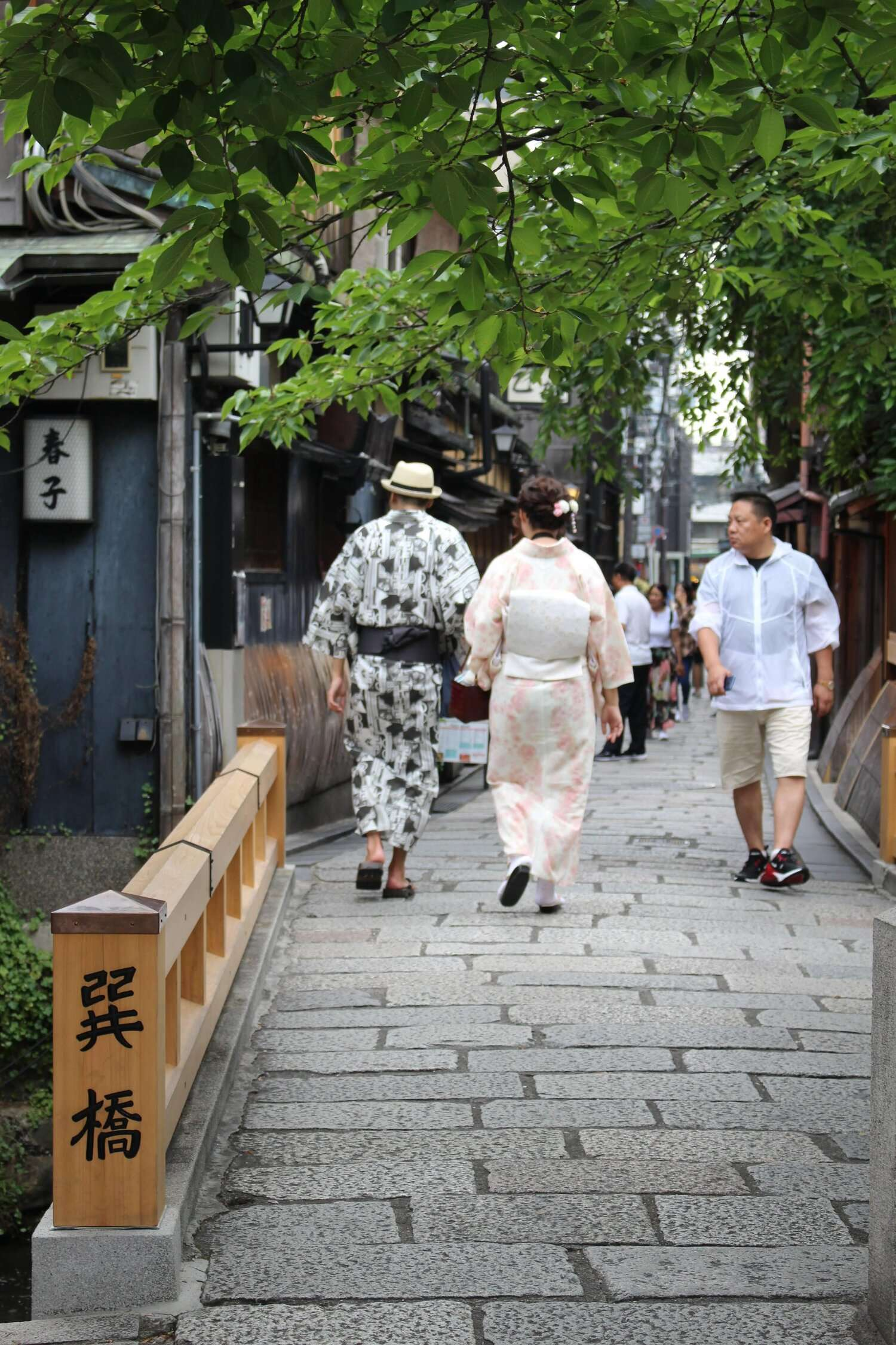 man and woman wearing traditional Japanese kimonos walk across a bridge in Kyoto's Gion District