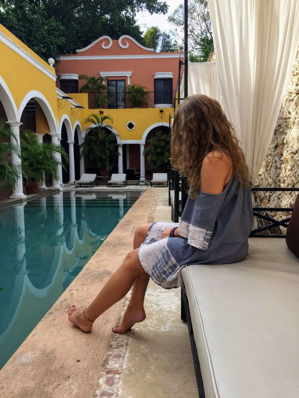 Girl sits next to the swimming pool at Hotel Hacienda Merida
