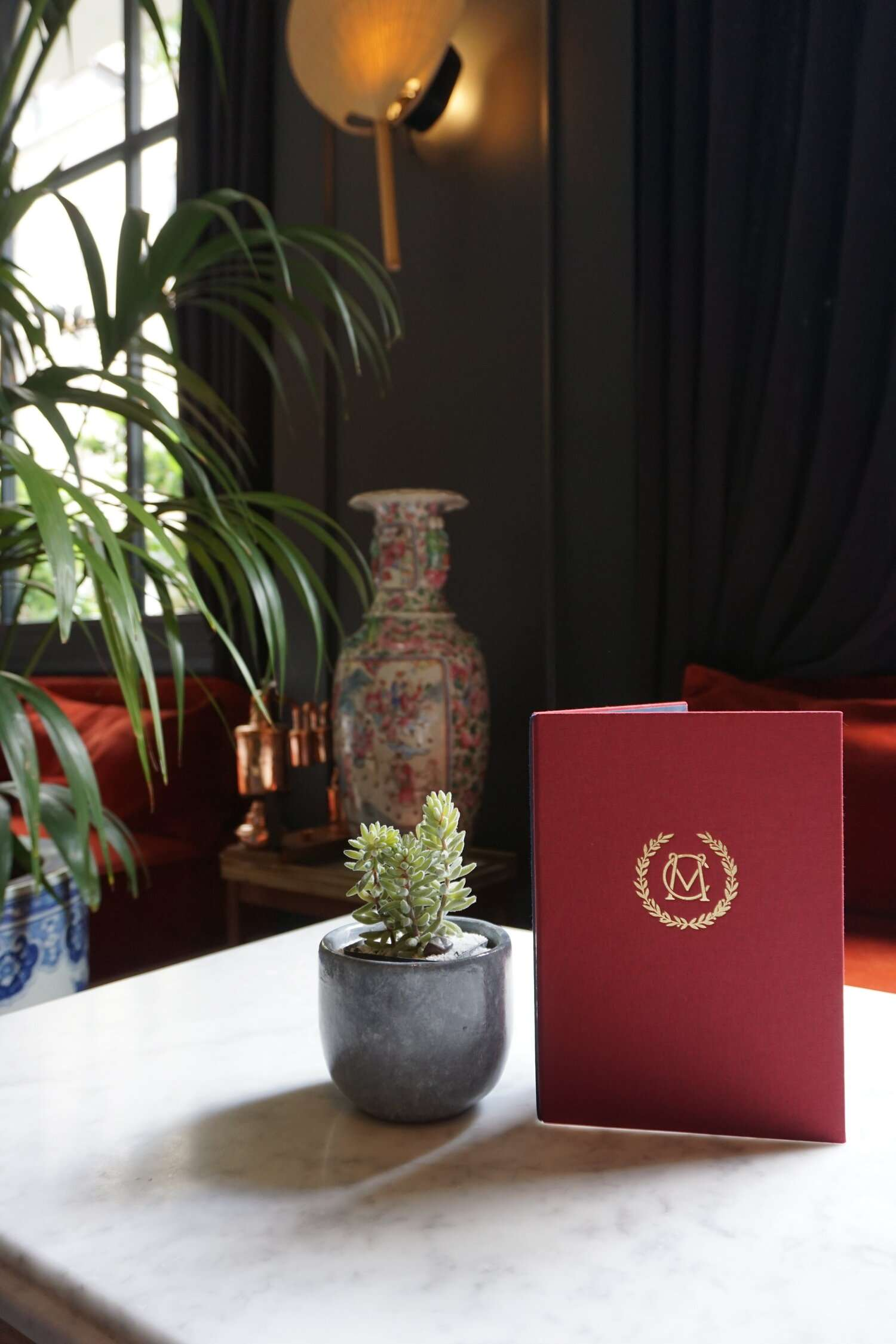 red menu beside a succulent on a table in the breakfast room at Hotel Monte Cristo Paris