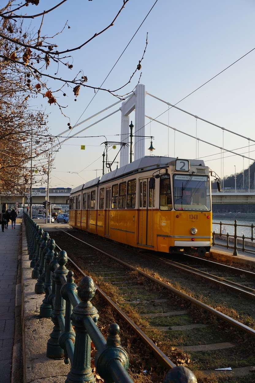 yellow and white tram along the waterside in Budapest