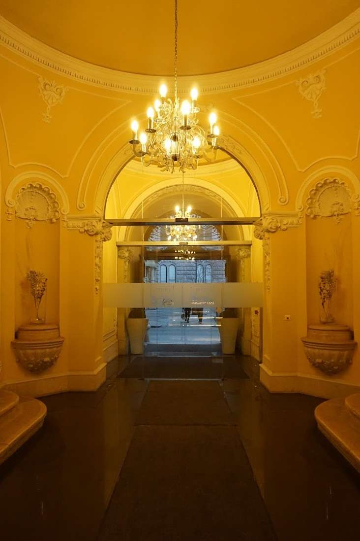 grand entrance to Hotel Palazzo Zichy Budapest with large chandelier lit with soft lighting