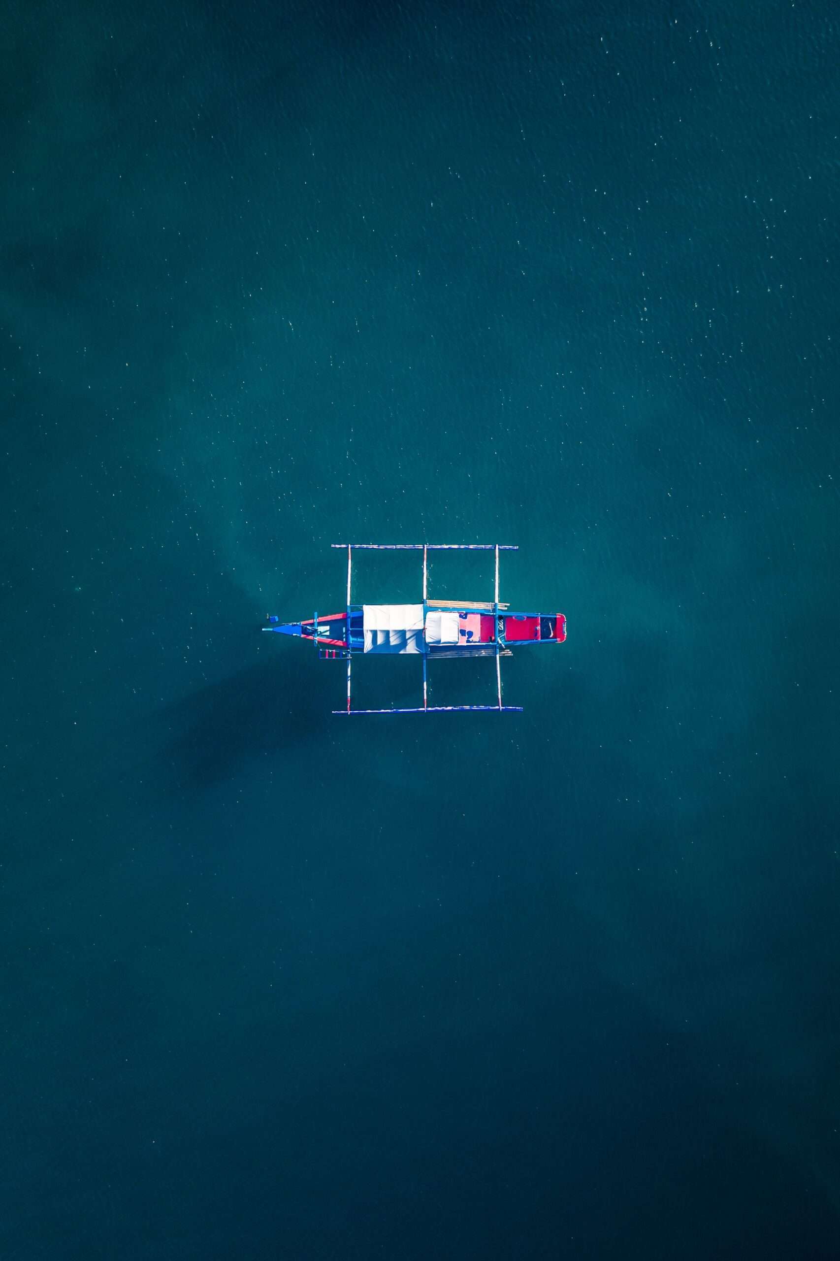 blue, white and red wooden boat on the water in Coron, Philippines