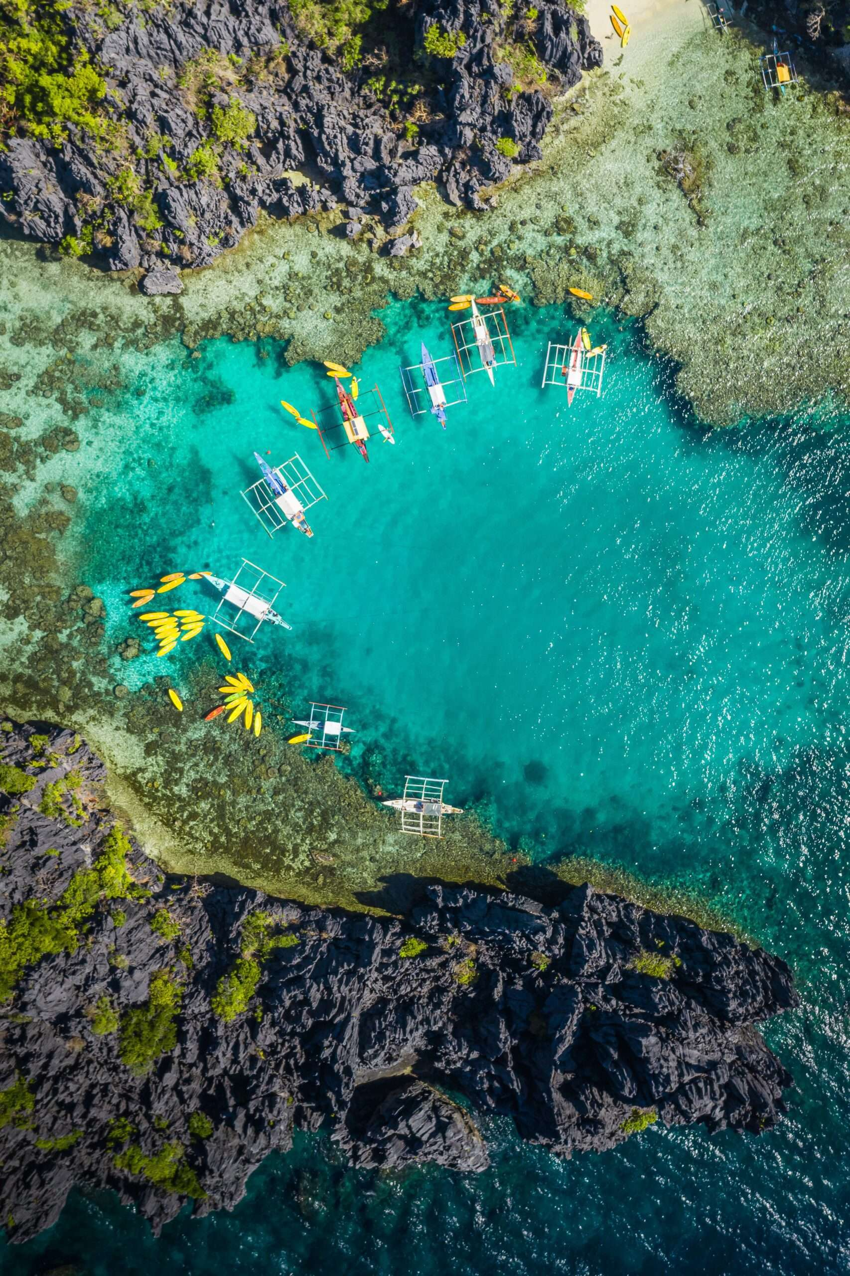 drone shot of a turquoise lagoon in Coron, with wooden boats and coral reefs