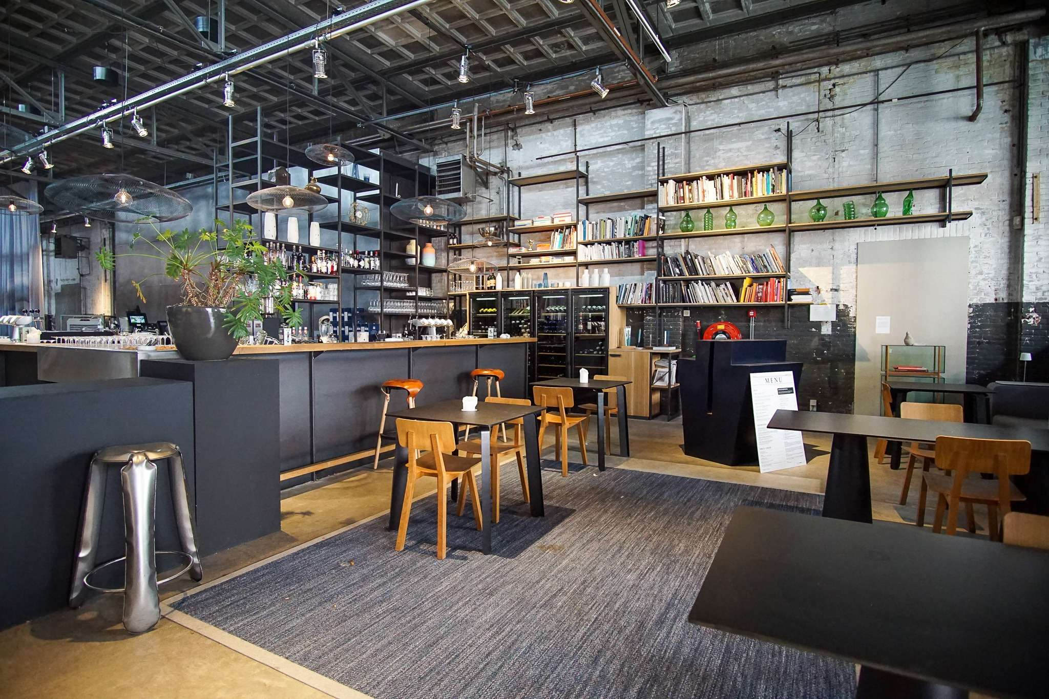 industrial chic themed bar with black and wooden furniture at Kazerne