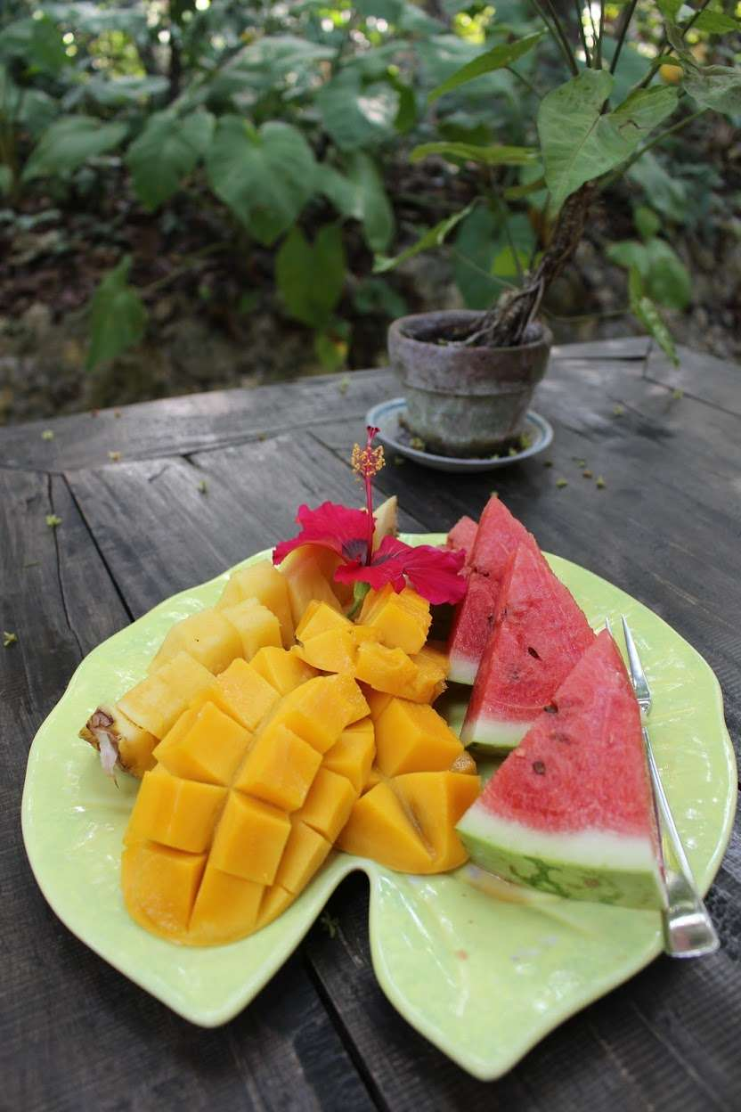 plate of fresh mango, pineapple and watermelon, decorated with a tropical flower at La Casita de Baclayon in Bohol, Philippines