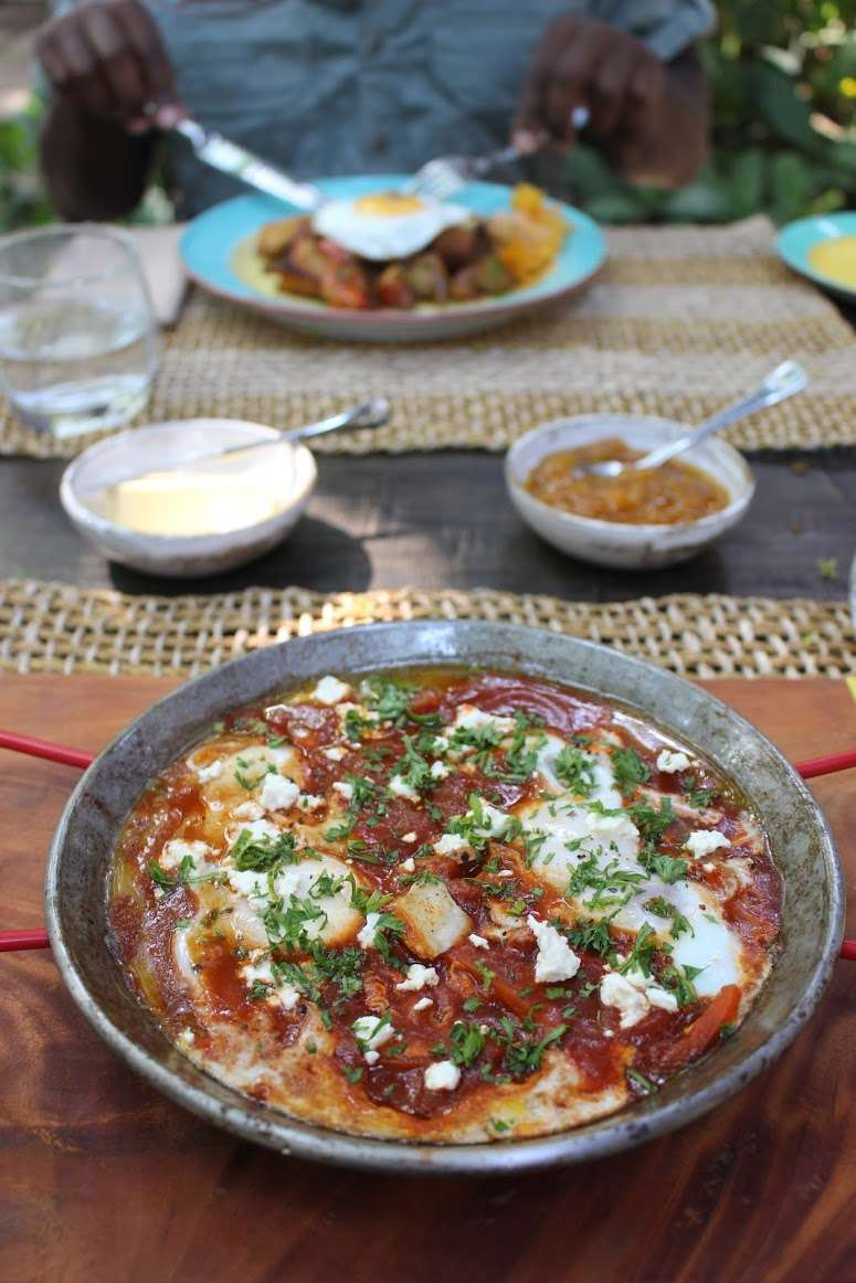Baked eggs in tomato sauce with fresh herbs, served for breakfast at La Casita de Baclayon in Bohol, Philippines