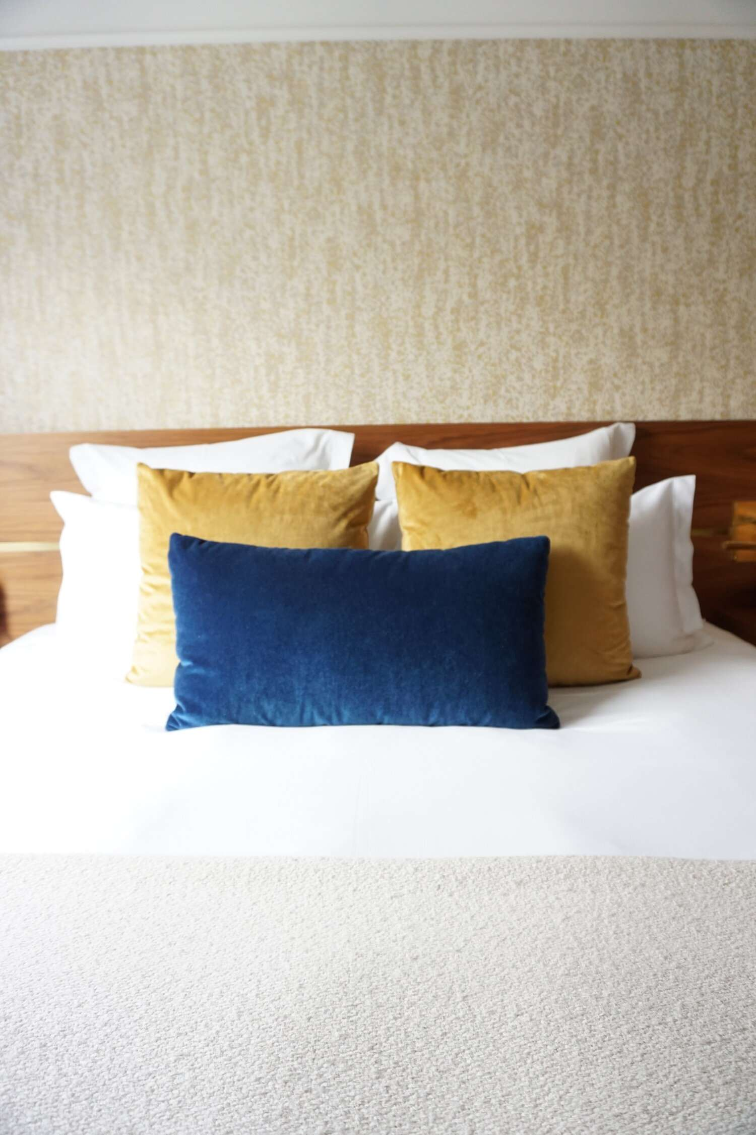 gold and blue cushions on the bed at Le Hotel Parister in Paris