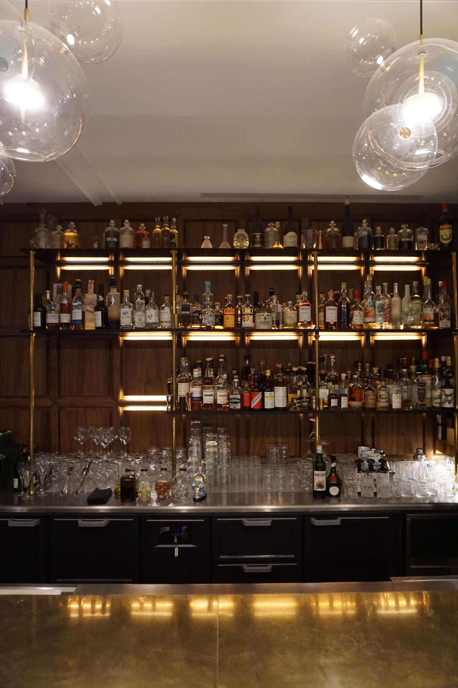 shelves filled with bottles behind the bar at Le Hotel Parister in Paris