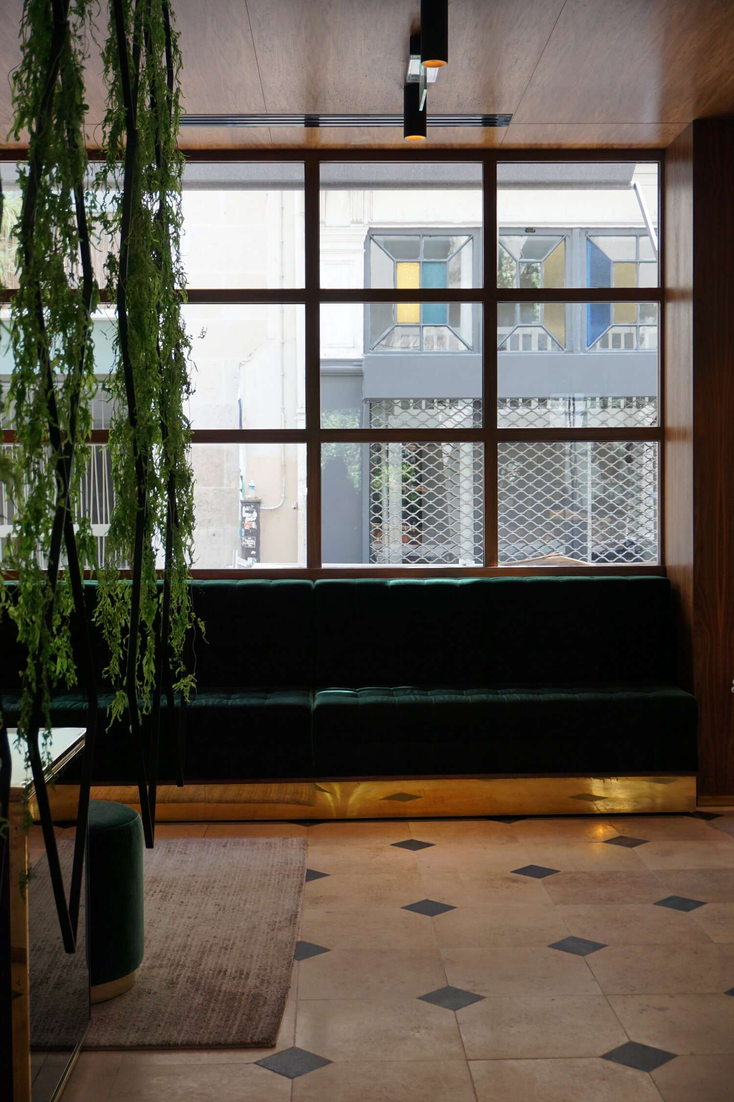 plants hang in the window in the foyer of Le Hotel Parister in Paris