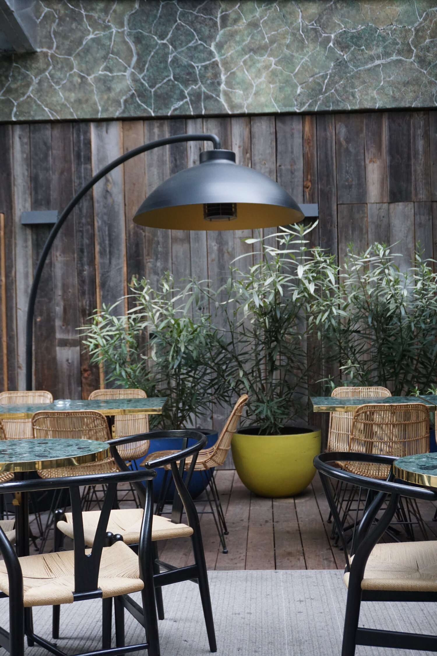 outdoor seating on a wooden deck with plants at Le Hotel Parister in Paris
