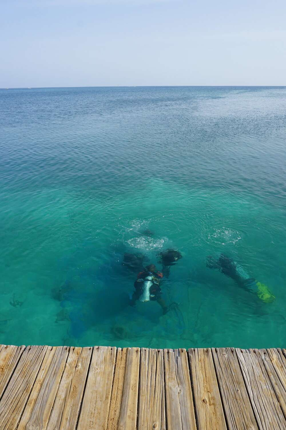 three scuba divers below the surface of the water just off the dock, whilst learning to dive in Utila