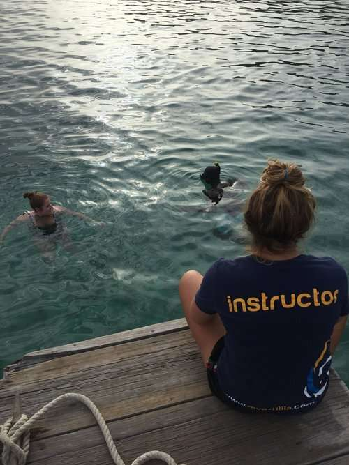 lady sitting on the edge of a dock wearing a tshirt saying 'instructor' as two people swim in the water before her