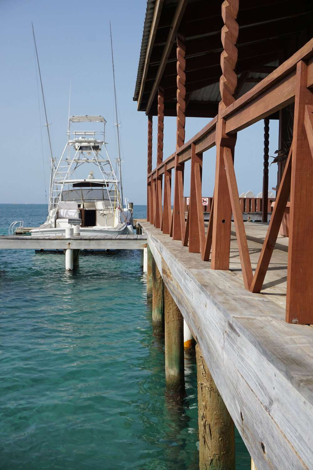 looking along the wooden dock with a white boat at the end, at Bay Islands College of diving in Utila