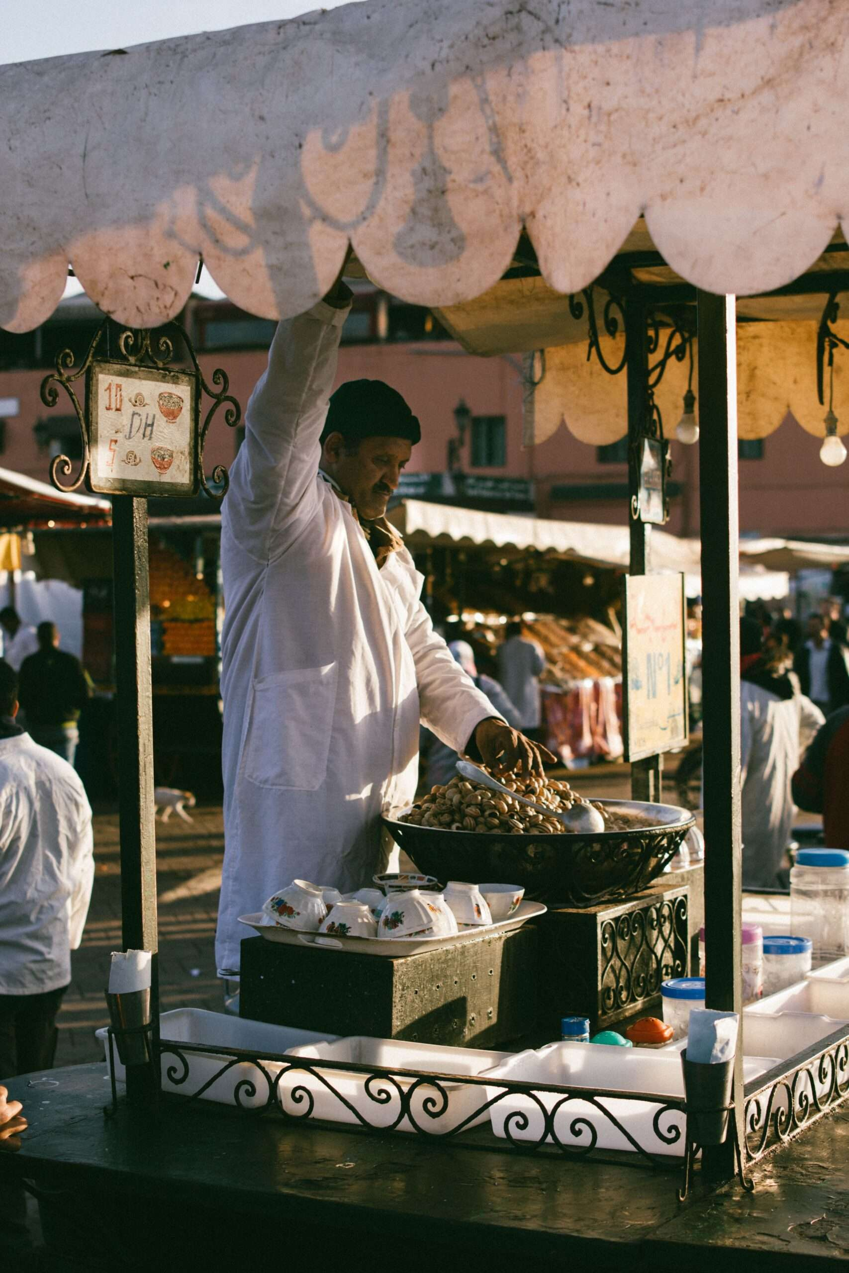 man wearing a white overcoat at a market stand in Marrakesh