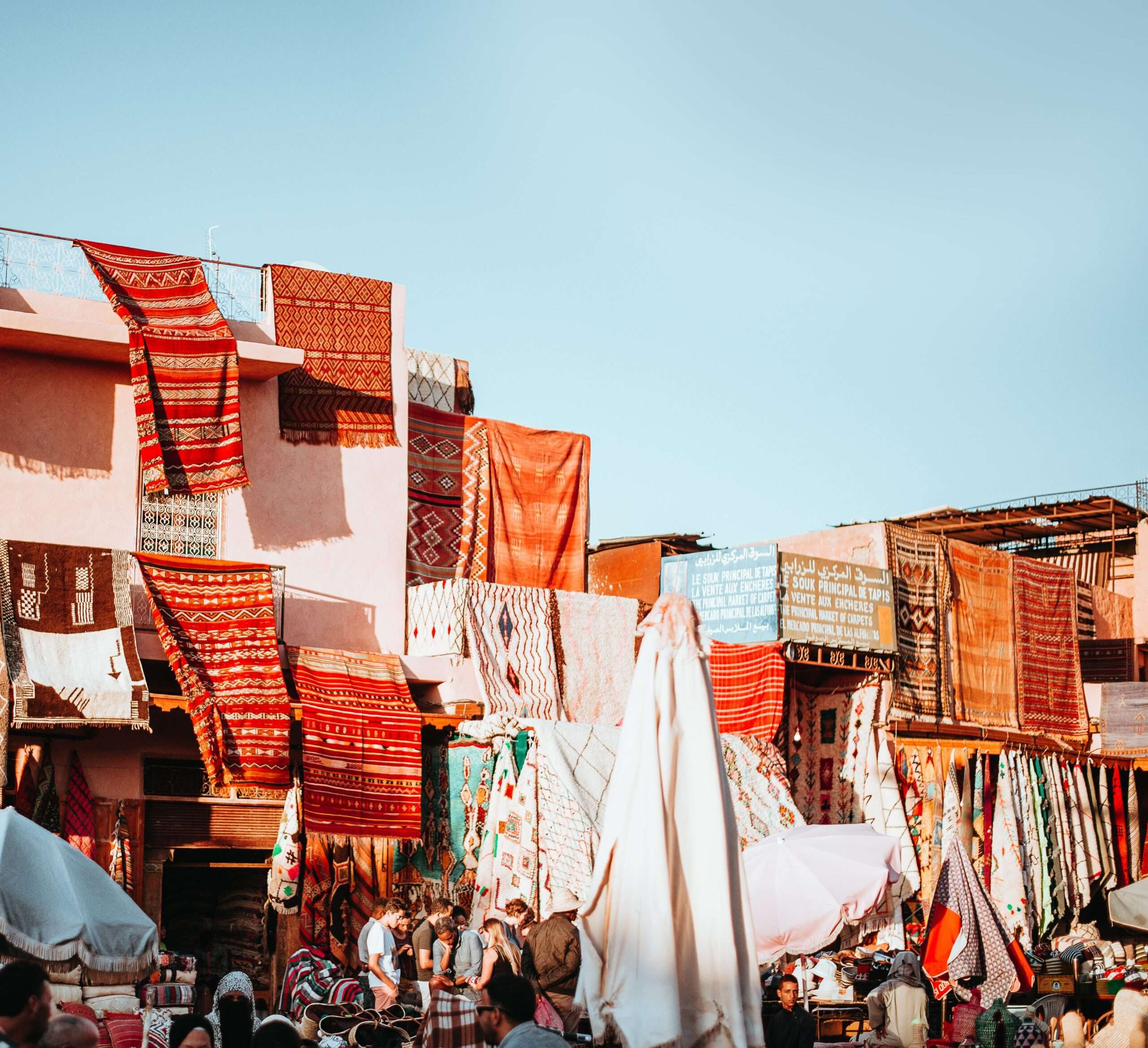 red patterned rugs hang across the front of a building at a market in Marrakesh