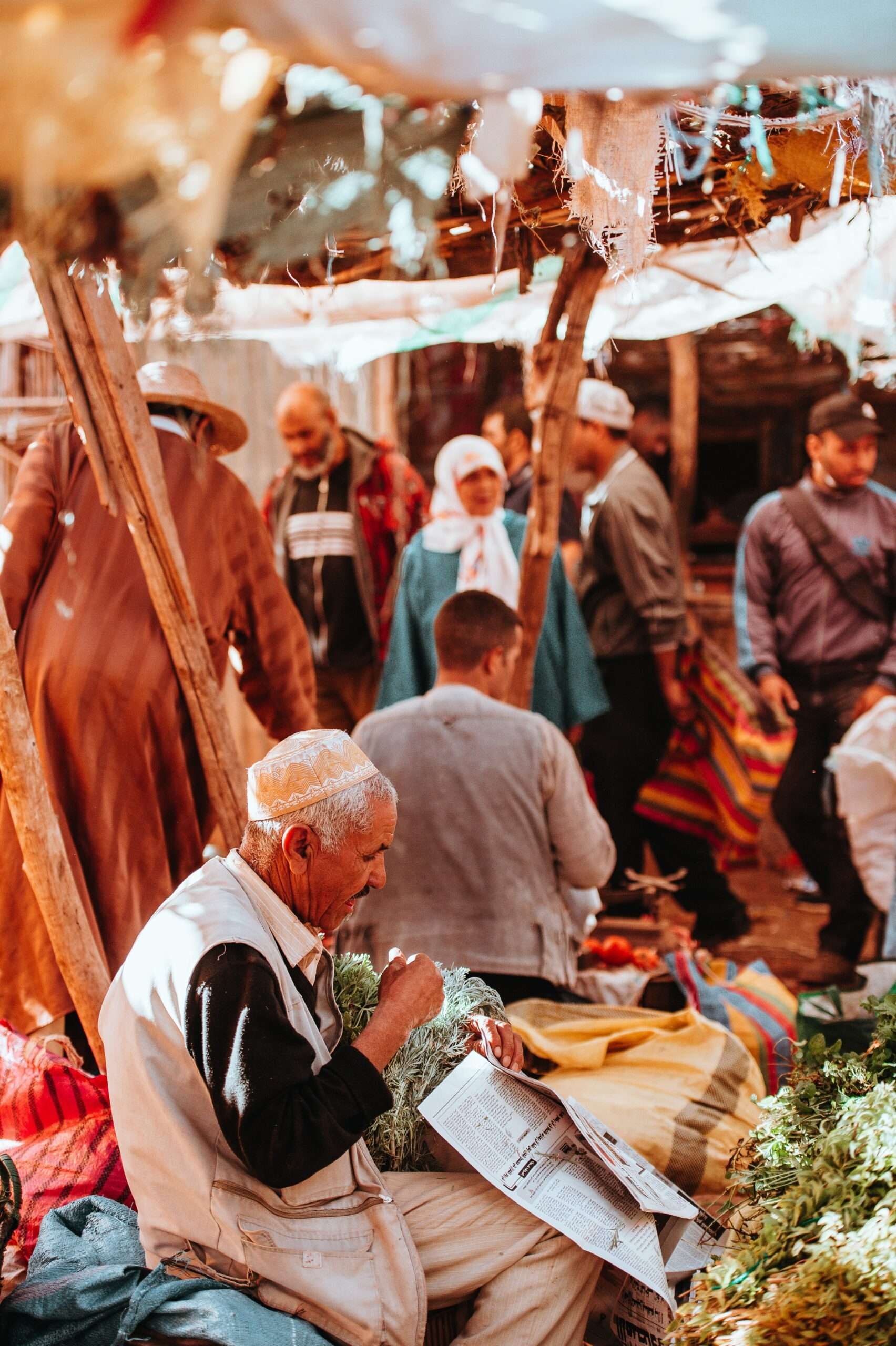 man with grey hair sits behind a stall at a busy market in Marrakesh