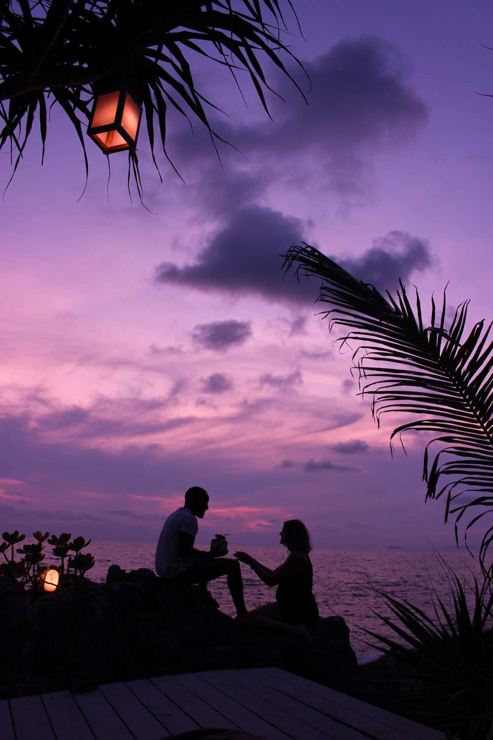 silhouette of a man and woman with a bright purple sunset sky over the sea at Moonlight Exotic Bay Resort, Koh Lanta
