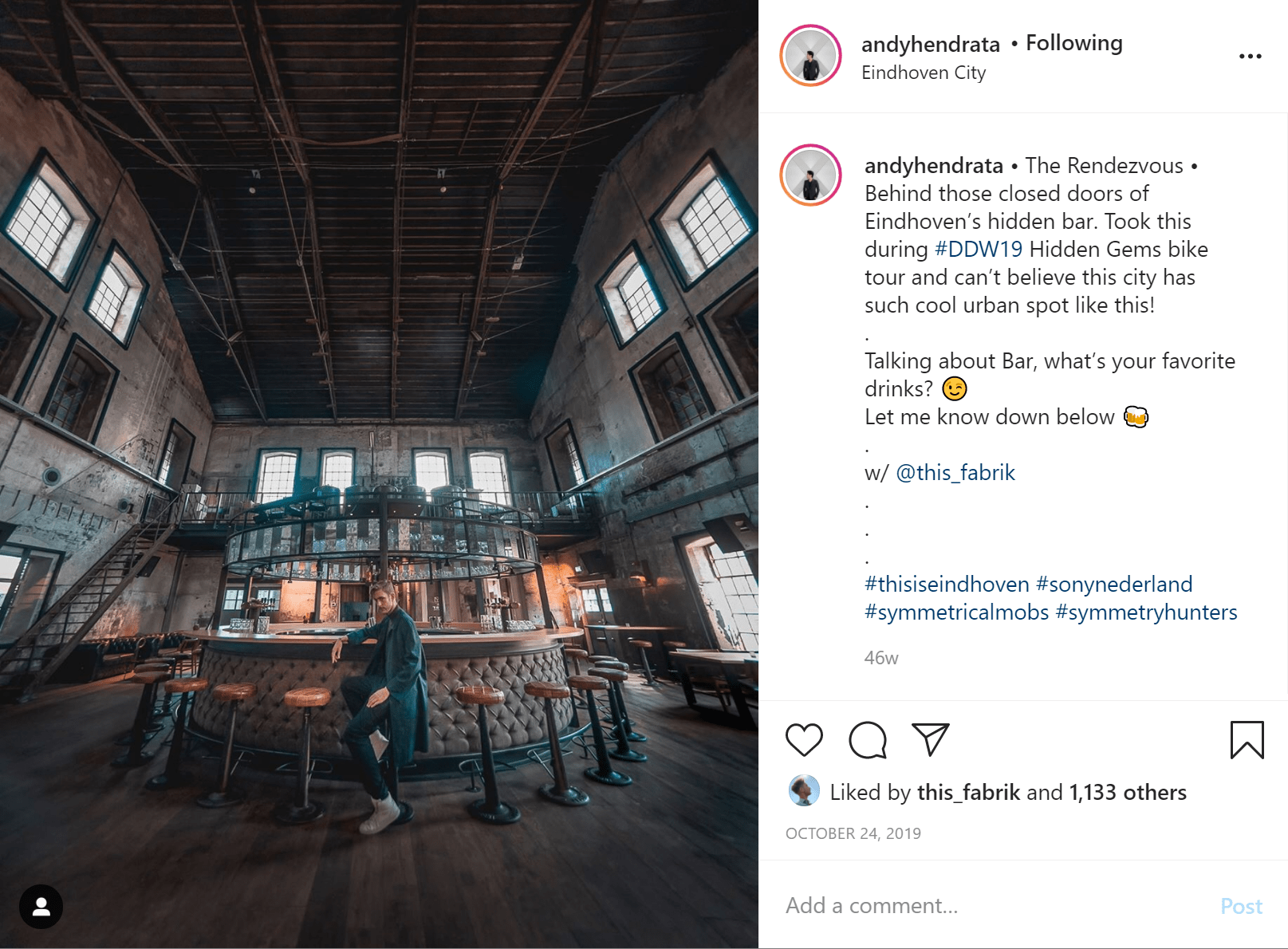 Man wearing a long black coat sits on a stool at a bar in a big industrial warehouse