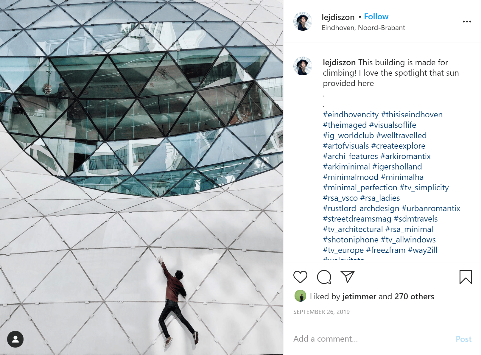 man wearing black jumping and reaching upwards in front of De Blob in Eindhoven - a modern building made with triangles of glass