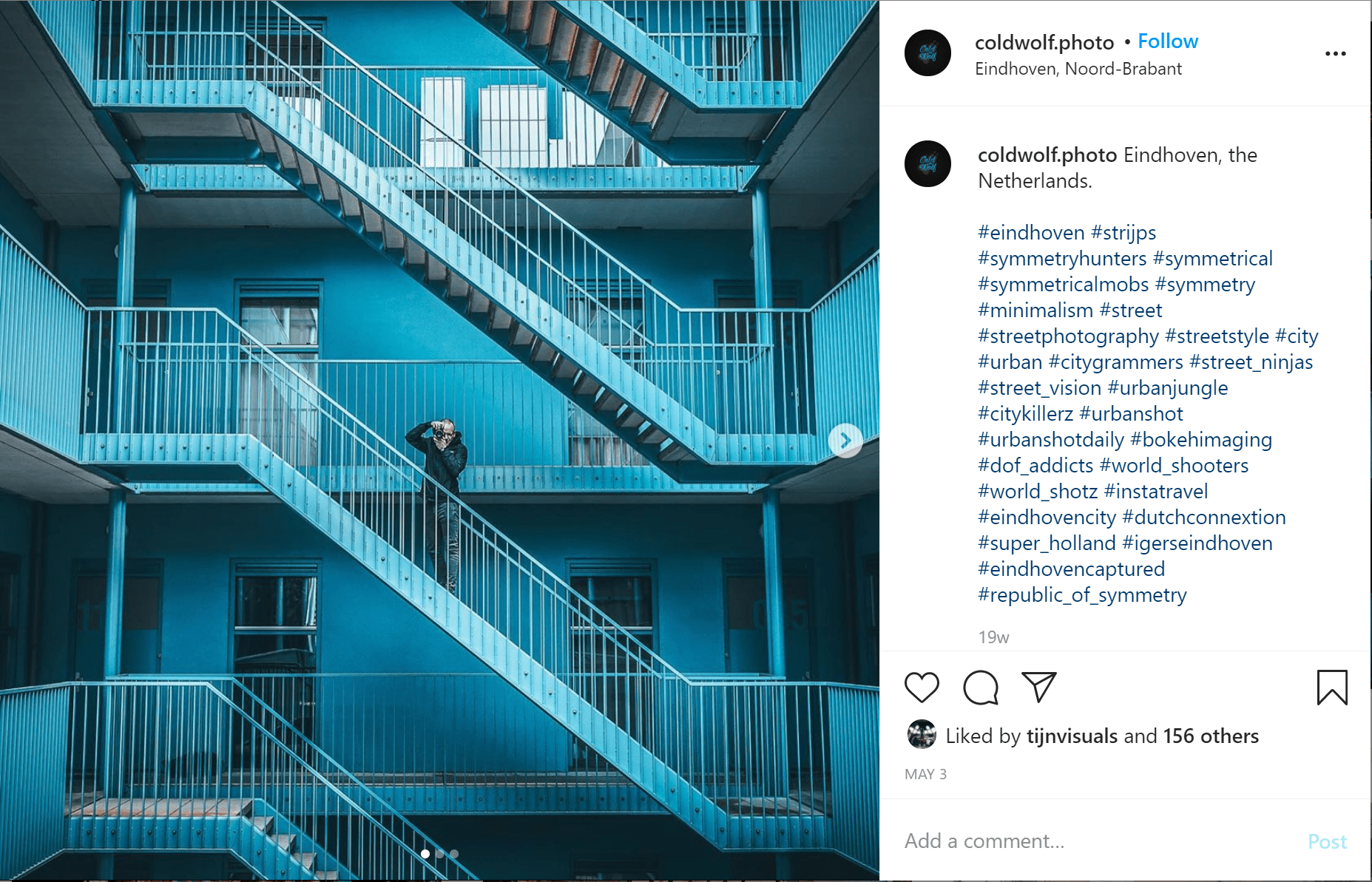 a man taking a photo, stood on blue metal stairs with another staircase above and below that one