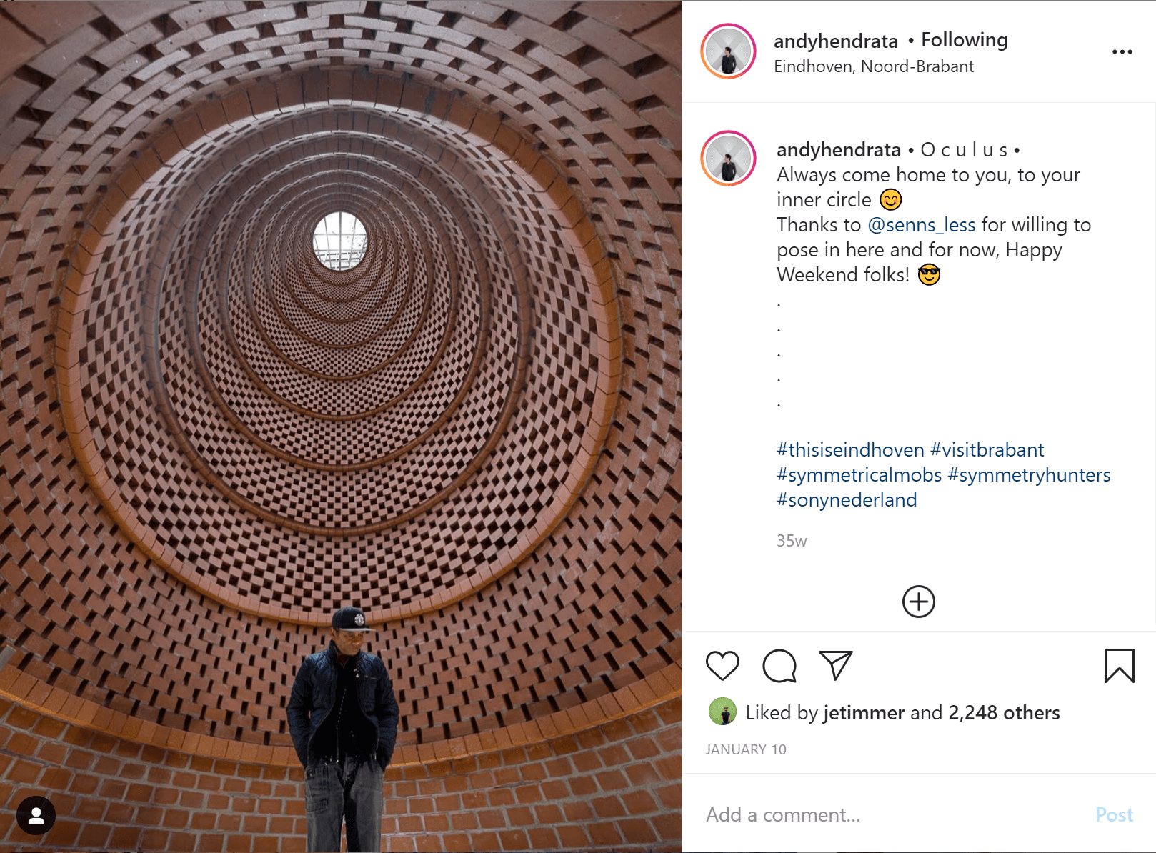 an instagrammable building, a man wearing black stands inside a tall circular structure made from red bricks